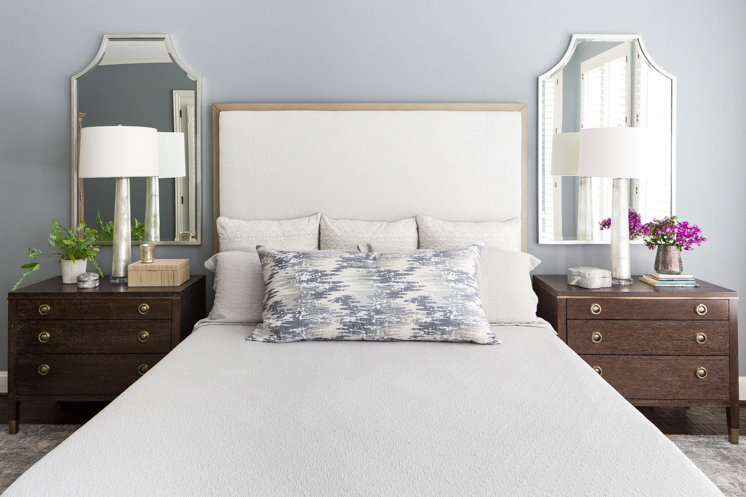 This soothing master bedroom makeover uses a cool blue-gray color palette with dark wood tones in the nightstands to anchor the look of the headboard wall. Carla Aston, Designer | Colleen Scott, Photographer