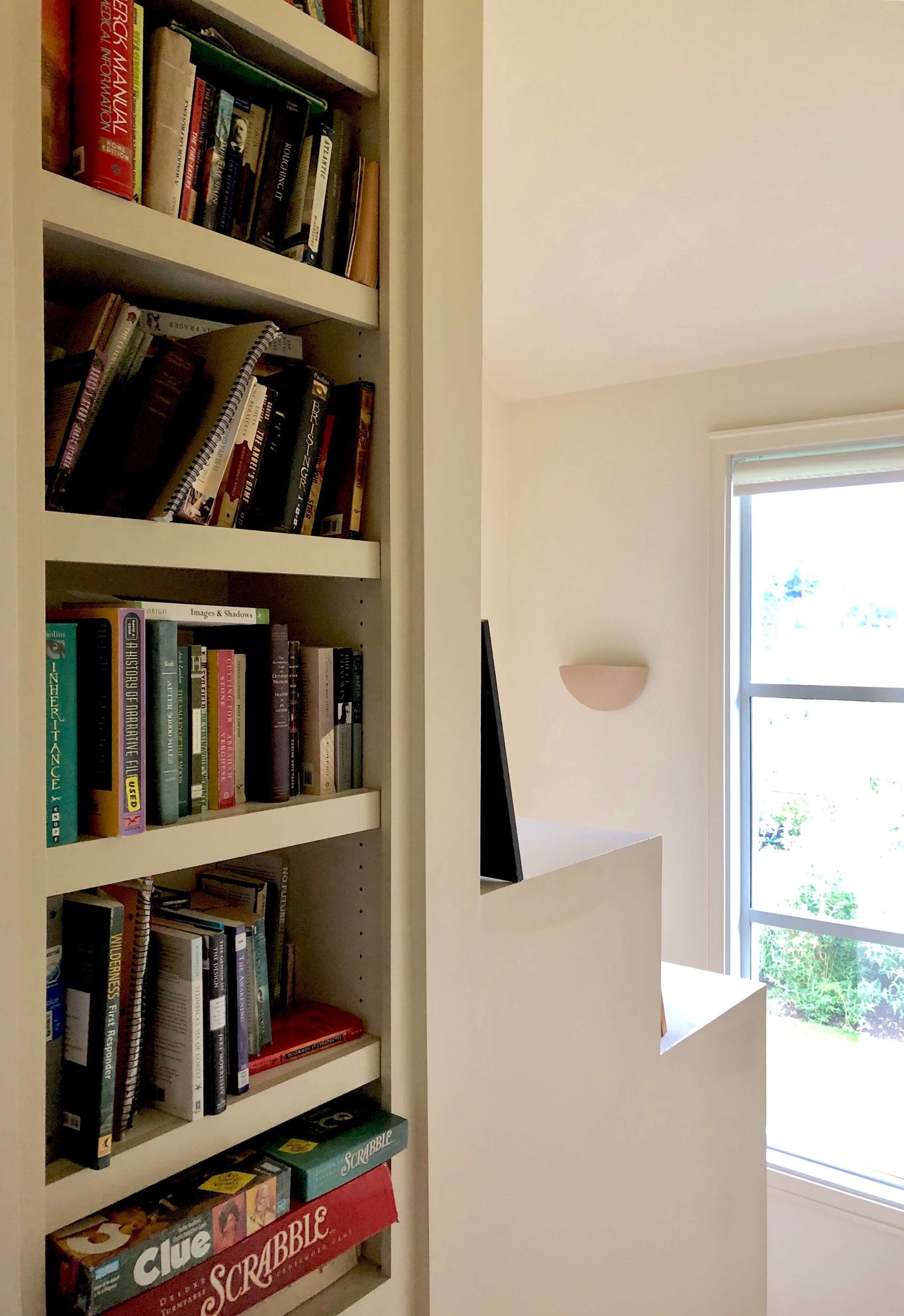 The central staircase with a tall window and more books and games in this Sonoma Valley Airbnb. #airbnb #winecountry