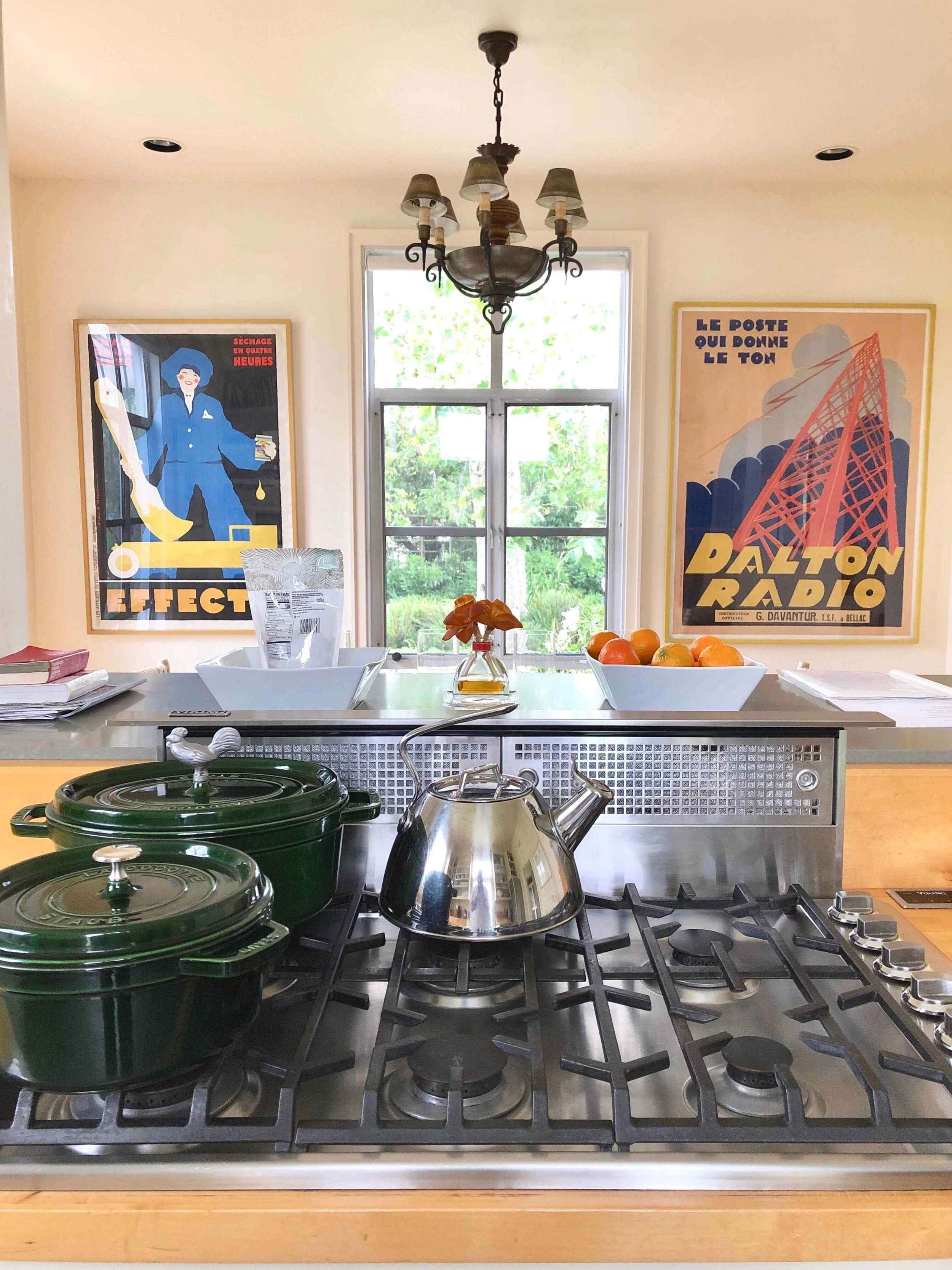 Here's the Viking cooktop with Staub hunter green cookware in the kitchen. Vintage French posters create a European ambience in this Sonoma Valley Airbnb vacation rental dining room (beyond the kitchen)..#airbnb #winecountry #farmhousekitchen