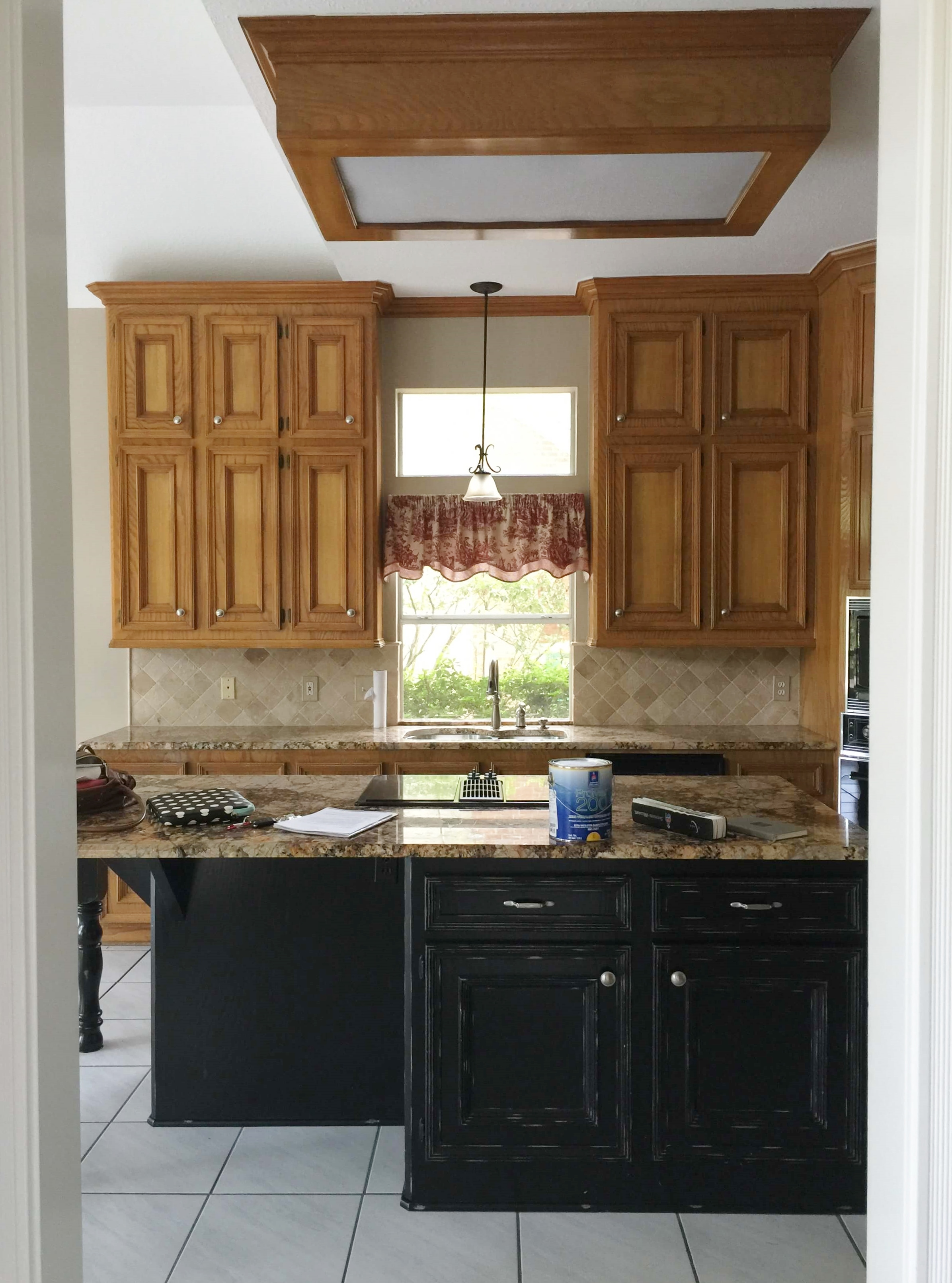 BEFORE - The kitchen window was chopped up with the transom above. A taller window would be the way to go here to make this kitchen feel more open and lighter overall.