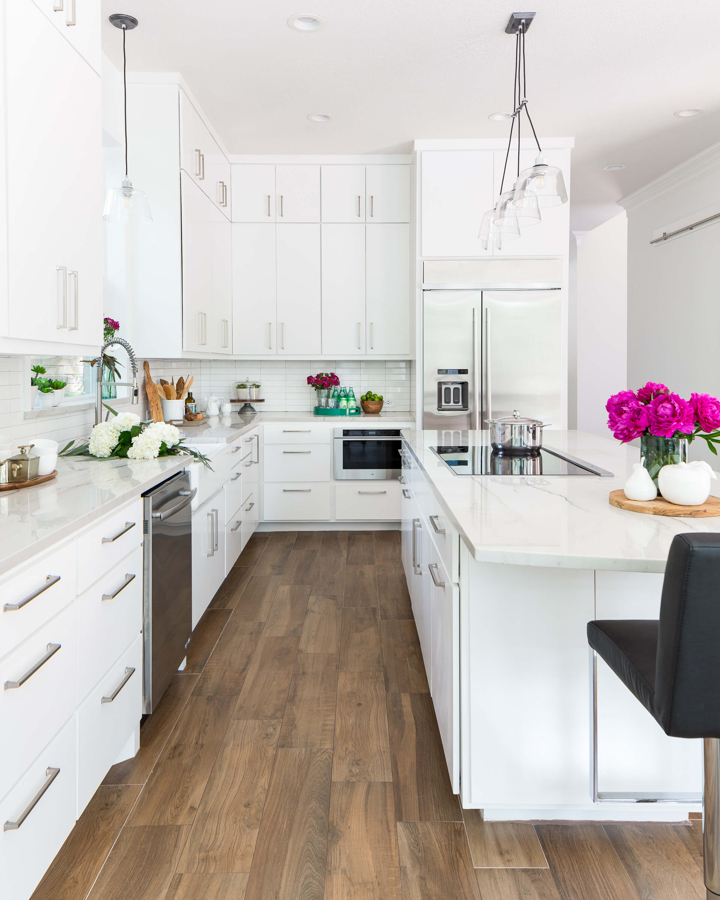 AFTER - This all white and bright kitchen was a big transformation from the dated wood kitchen here previously. See the transformation! Carla Aston, Designer | Colleen Scott, Photographer #whitekitchen #kitchenideas