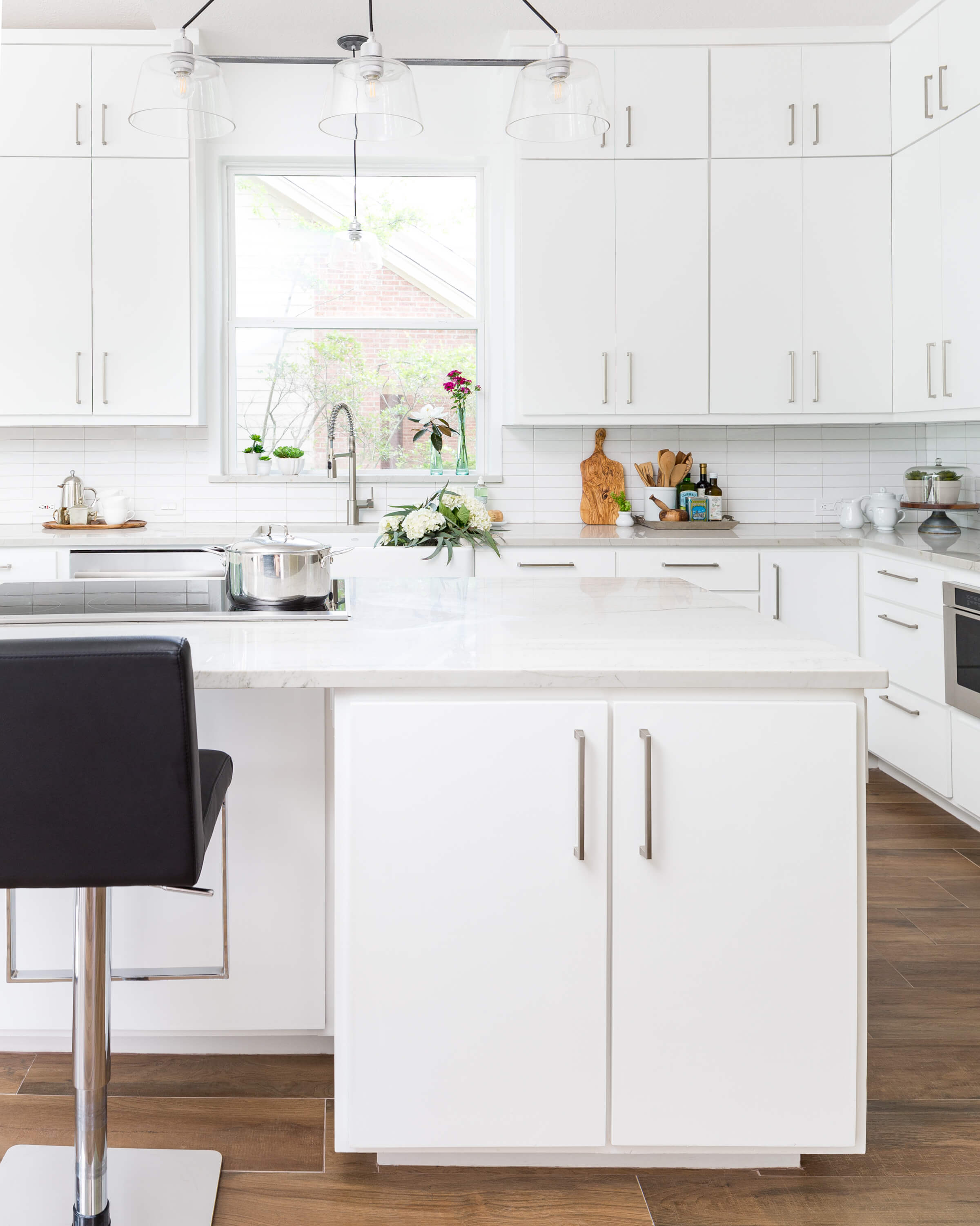 AFTER - The homeowners were after a white kitchen and that is exactly what they got! Simple details, white cabinetry and a linear stacked tile make for a simple look. Carla Aston, Designer | Colleen Scott, Photographer #whitekitchen #kitchenideas