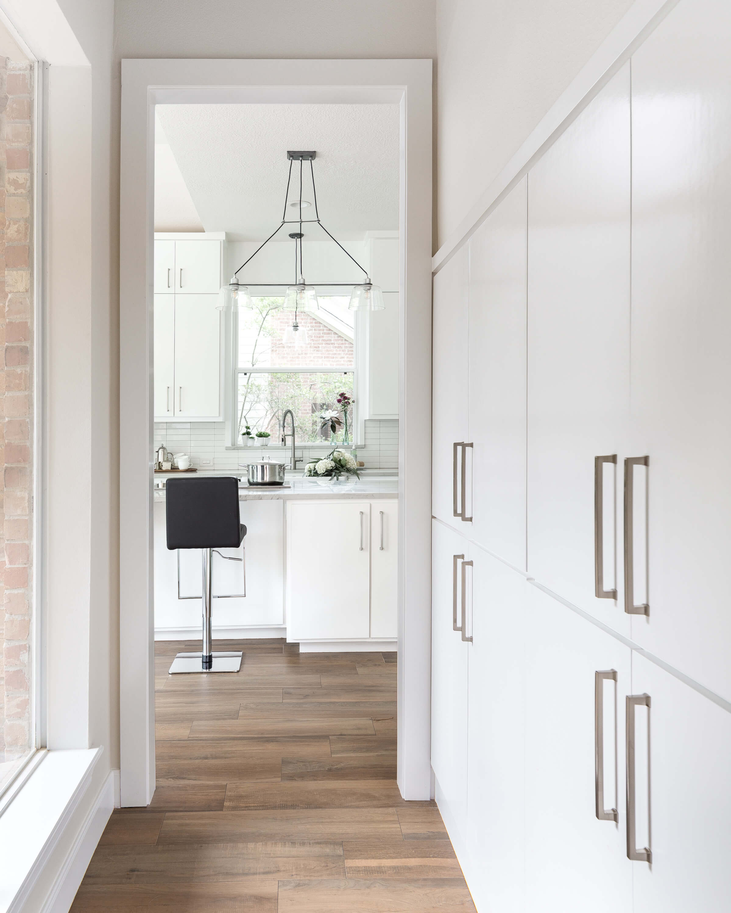 AFTER - You can see that we just filled in the opening under the stairs with full height cabinetry to minimize that look of the short space. It provided a lot more storage too. Carla Aston, Designer | Colleen Scott, Photographer #whitekitchen #kitchenideas