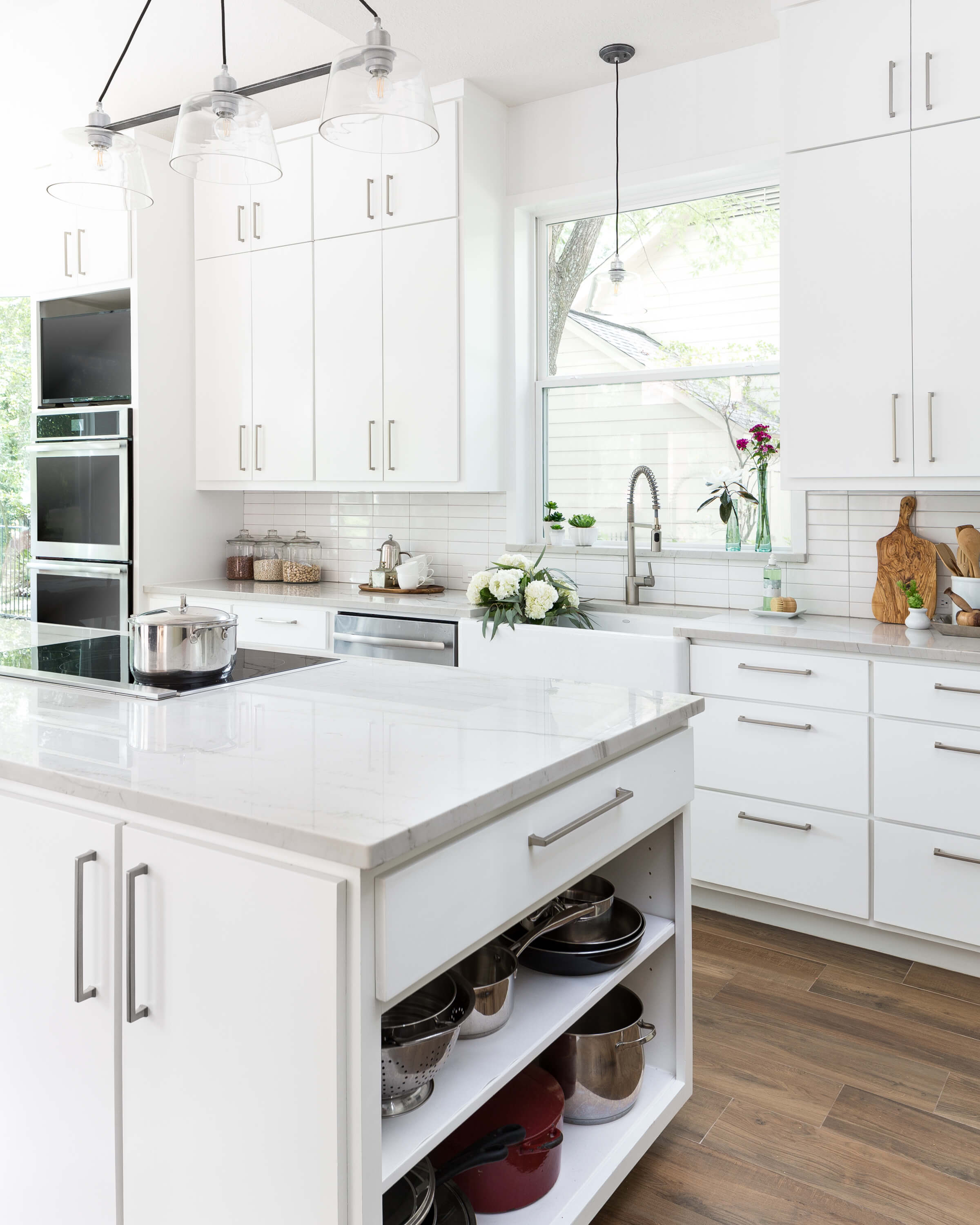 AFTER - The desired open shelving for pots and pans was tucked in at the end of the island to hide the clutter and make these easily accessible for the homeowner. The new taller window and farmhouse sink are nice additions. Carla Aston, Designer | Colleen Scott, Photographer #whitekitchen #kitchenideas