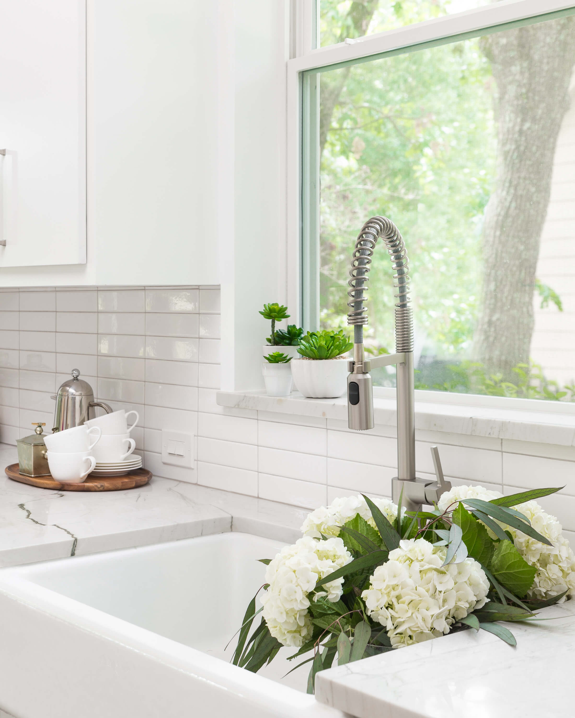 AFTER - Simple, stacked linear subway tile makes for a contemporary look in this white kitchen. Natural stone quartzite countertops add some warmth and a natural element to the contemporary space. A sill made in the same counterop material adds protection from water at the kitchen sink. Carla Aston, Designer | Colleen Scott, Photographer #whitekitchen #kitchenideas