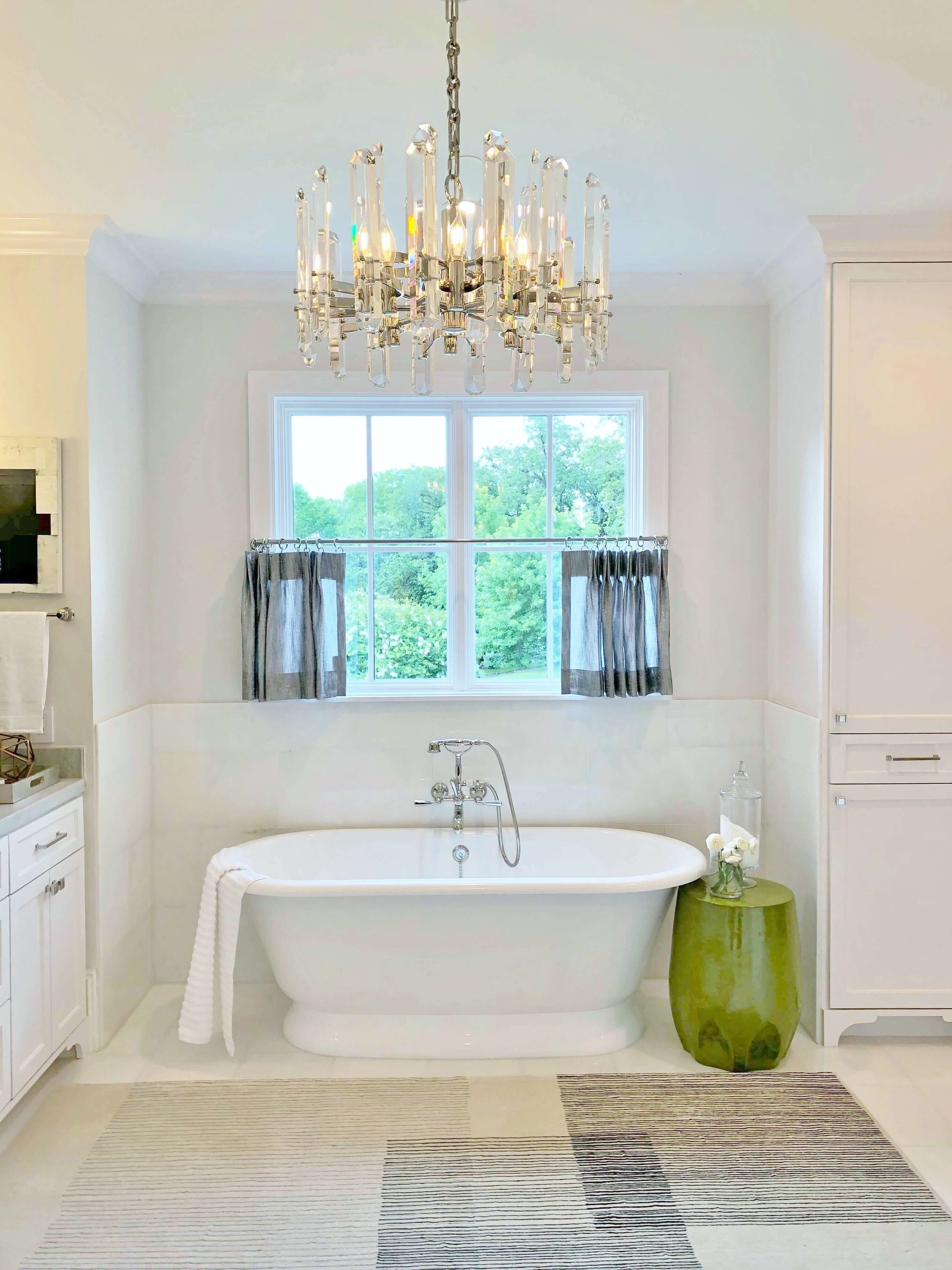 This beautiful master bath with a free-standing tub, pretty cafe curtain and glam light fixture, designed by Brooke Bowman of Bowman Design Studio, fits the luxurious feel of this home in River Oaks, Houston. ASID River Oaks Showhouse #masterbath #bathdesign #freestandingtub
