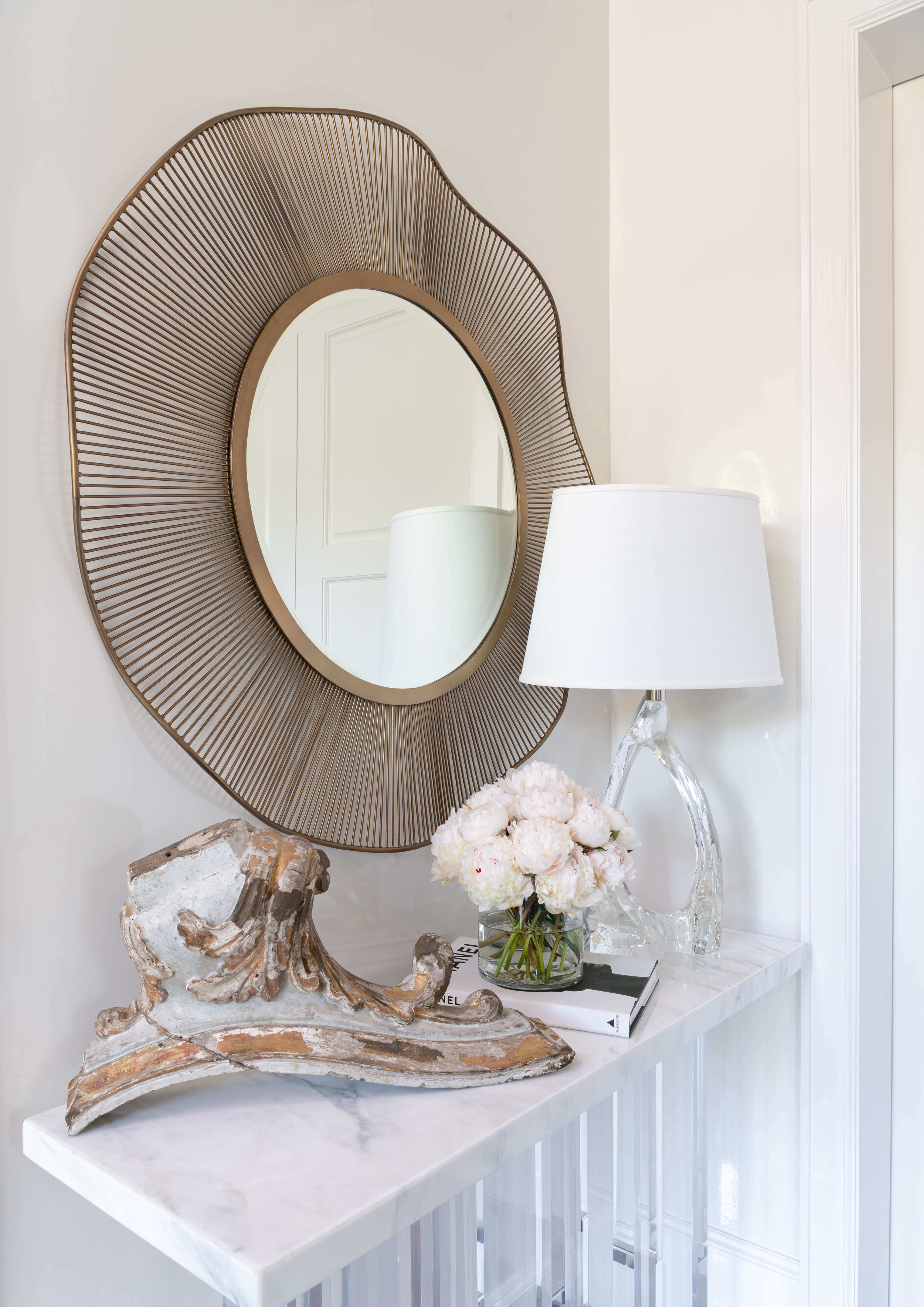 A beautiful vignette greets you at the entryway with a marble topped console, sculptural round mirror, and pretty accessories, designed by Talbot Cooley, in the ASID River Oaks Showhouse. | Photographer - Michael Hunter #foyer #entryhall #roundmirror