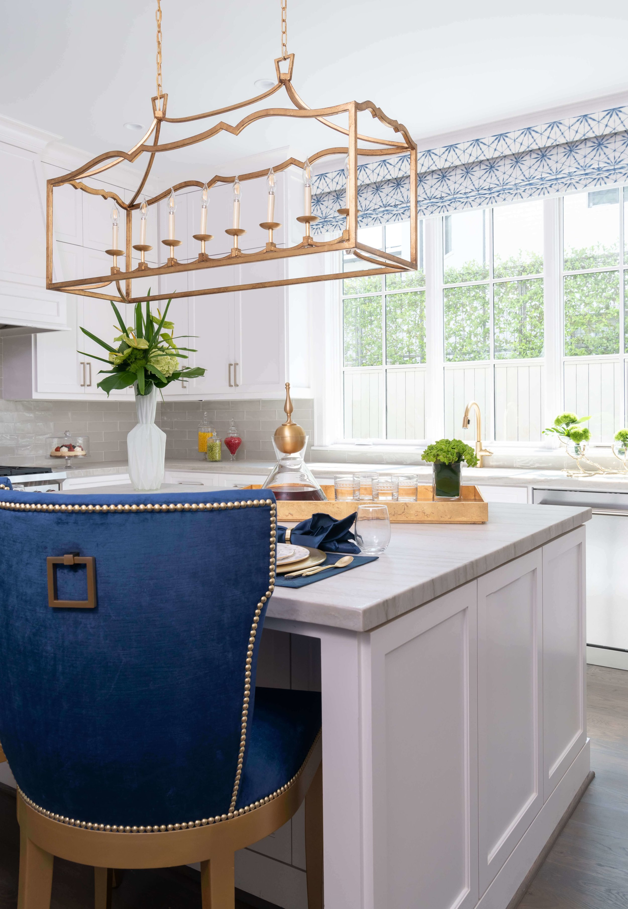 Bold blue counterstools and a gilded lantern bring color and warmth to this white kitchen space, designed by Missy Stewart. ASID River Oaks Showhouse | Photographer - Michael Hunter #kitchen #whitekitchen #counterstool