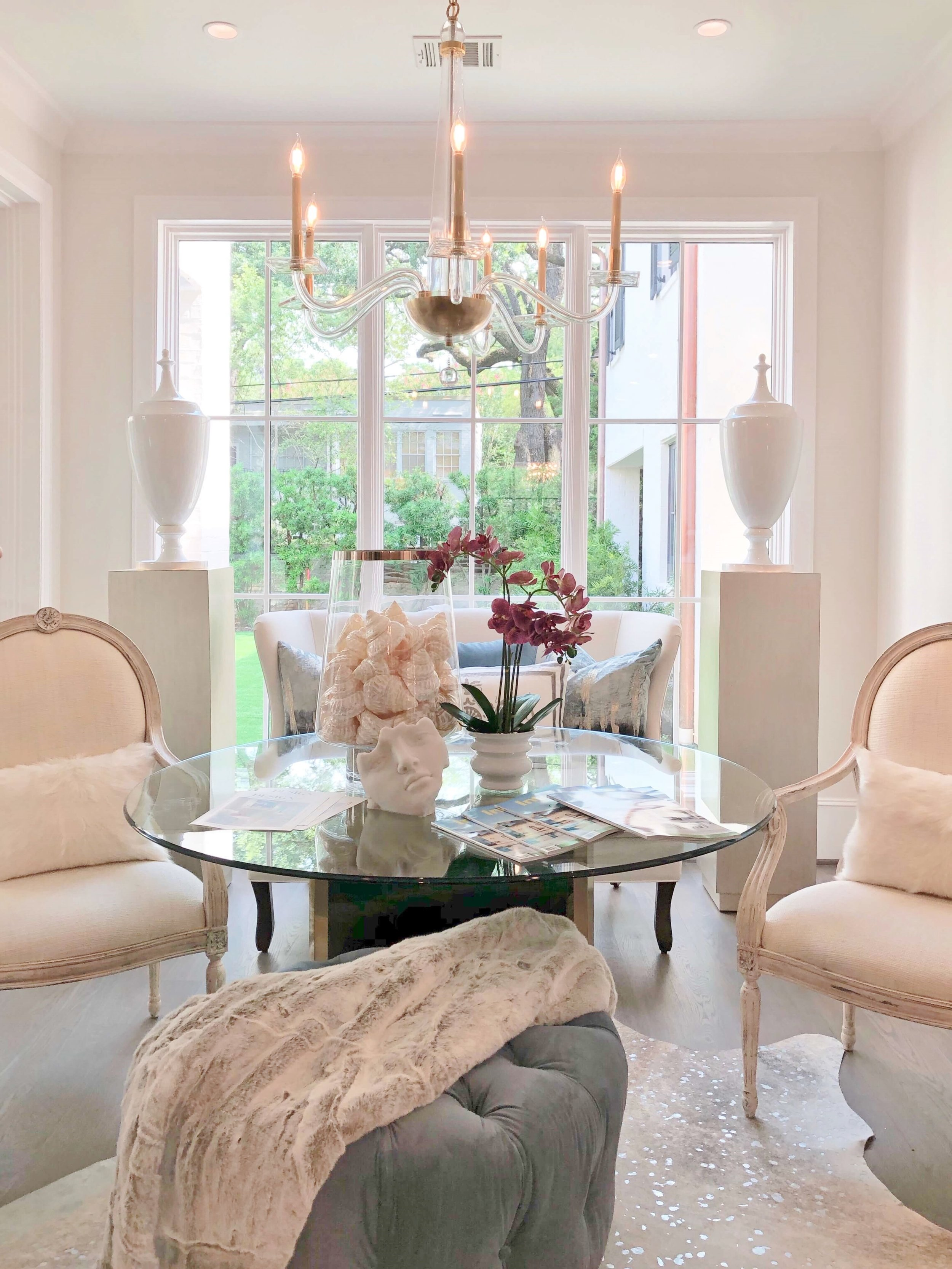 The breakfast area had a glamorous look with the velvet tufted ottoman, silver touches on the cowhide rug, and clear glass in the table top and chandelier. Lovely and light-filled, it was designed by The Design Firm. ASID Showhouse | #glamdecor #glasstable #velvetottoman #whitedecor