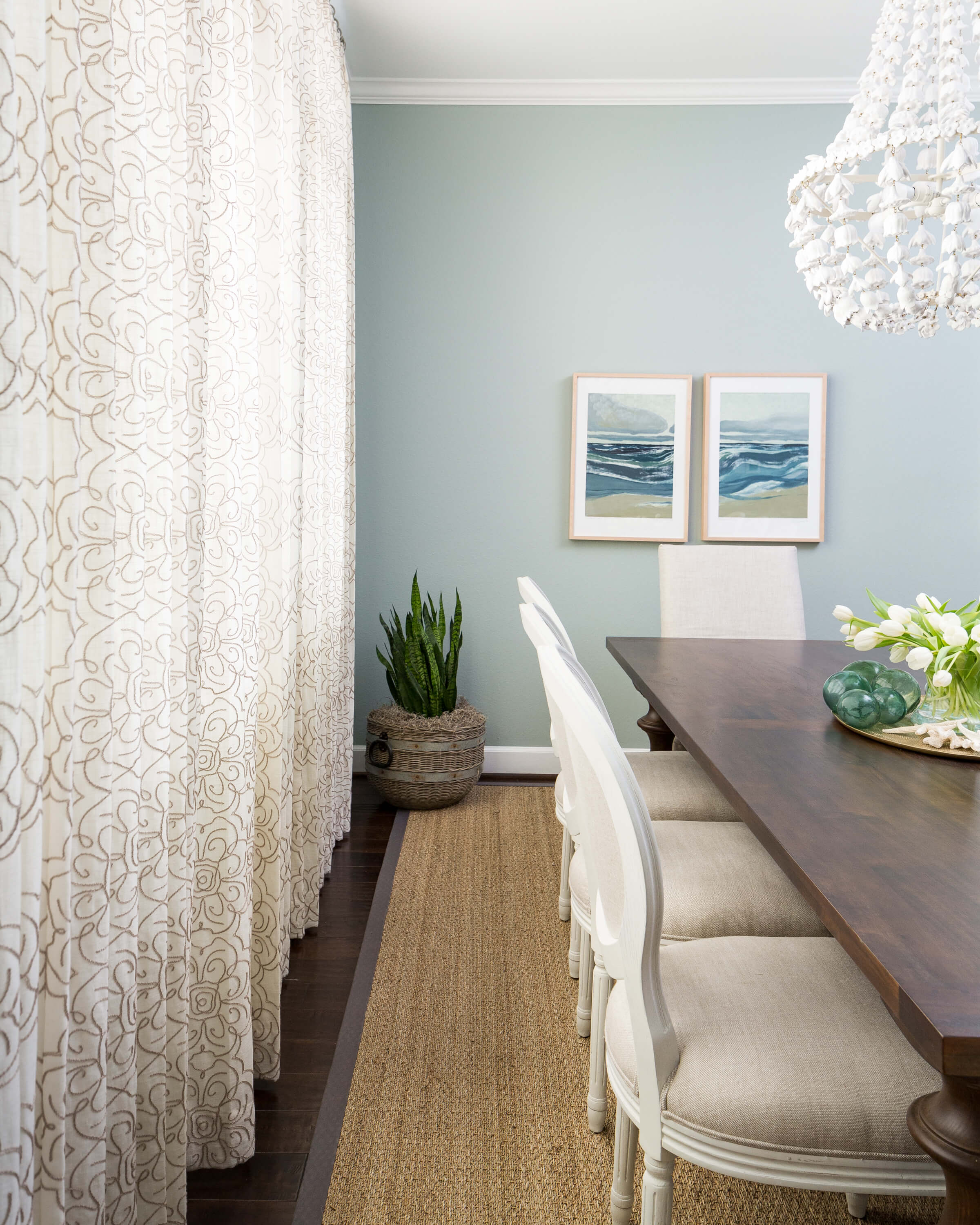 Crewel work sheer drapery panels add softness and subtle pattern in this coastal style dining room. Designer: Carla Aston, Photographer: Colleen Scott | #diningroom #coastalstyle #crewelwork #sheerdrapery #windowtreatment