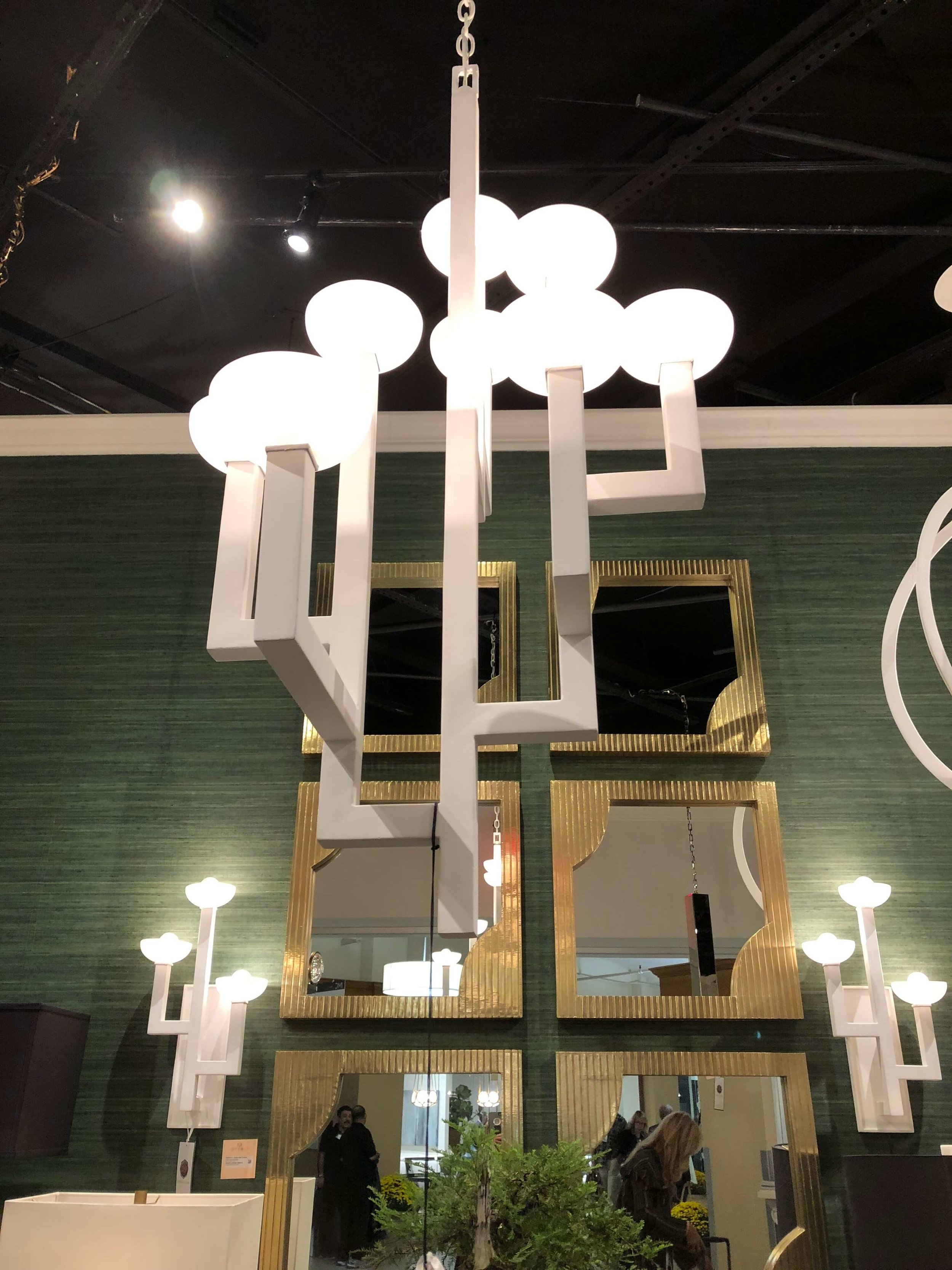 Currey and Co. showroom at Highpoint Market with white plaster chandelier and wall sconces, designed by Denise McGaha.