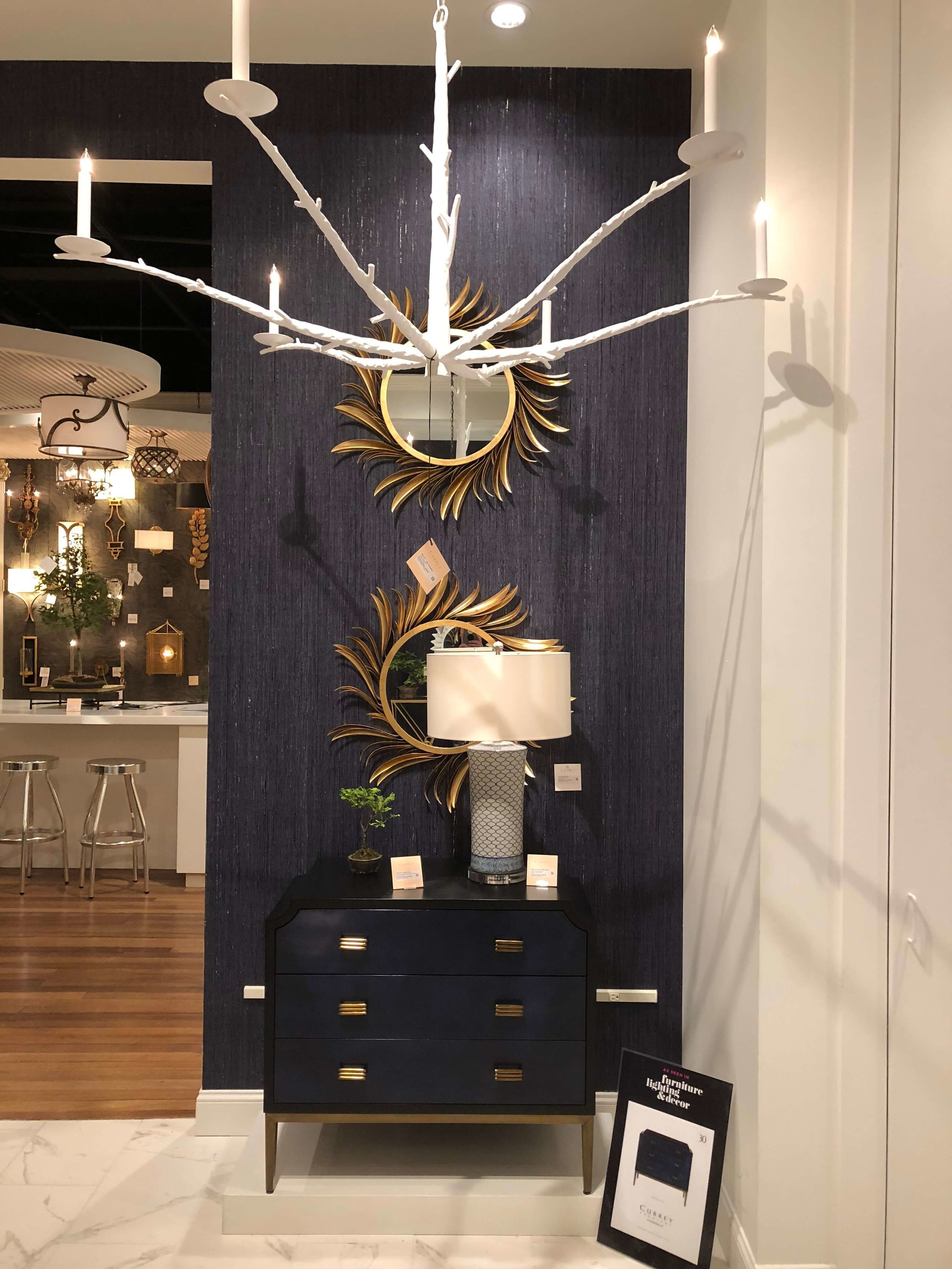 White plaster chandelier at Currey and Co. showroom at Highpoint Market.