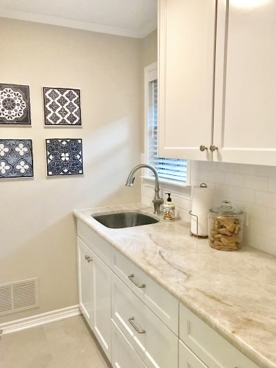 Laundry room makeover with Taj Mahal countertops, white subway tile backsplash and white cabinets to the ceiling | Designed in a Click Consultation #laundryroom #laundryroomideas