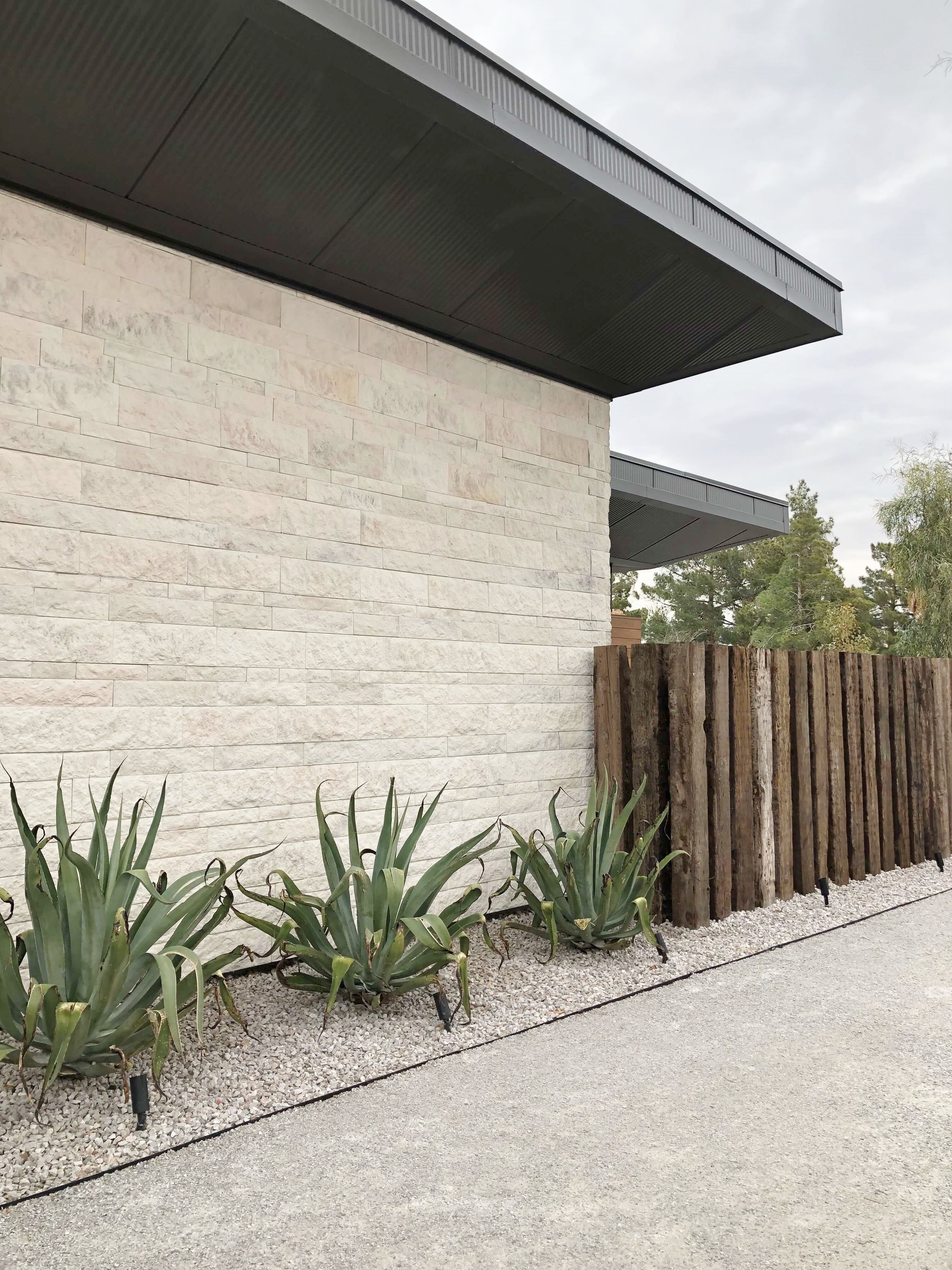 Stone walls, rugged railroad tie vertical fencing, gravel and succulents form the exterior views of the house from the street. The New American Remodel 2019 #hometour #railroadties #contemporaryhome