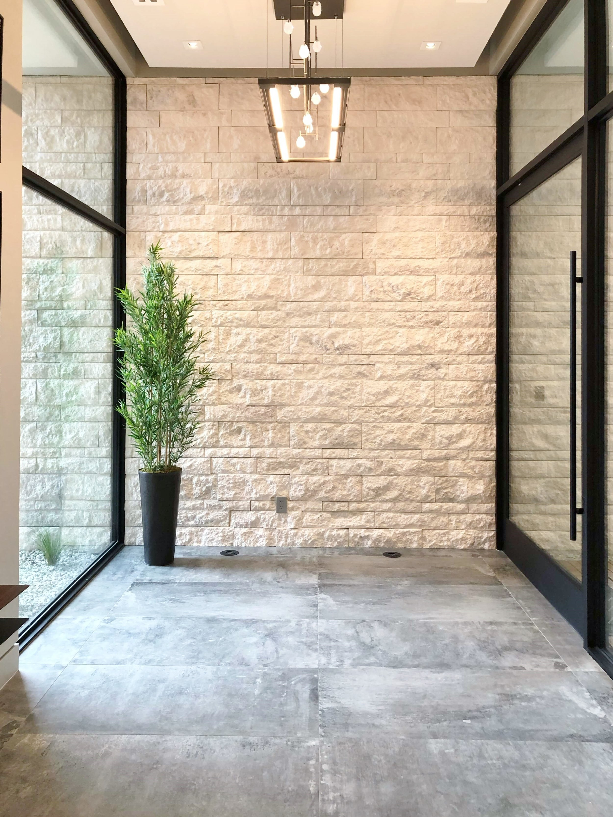 The wide front door opens to a view of the patio beyond. Textural, rugged materials combined with large glass walls create interest in this home. The New American Remodel 2019 #hometour #foyer #contemporaryhome