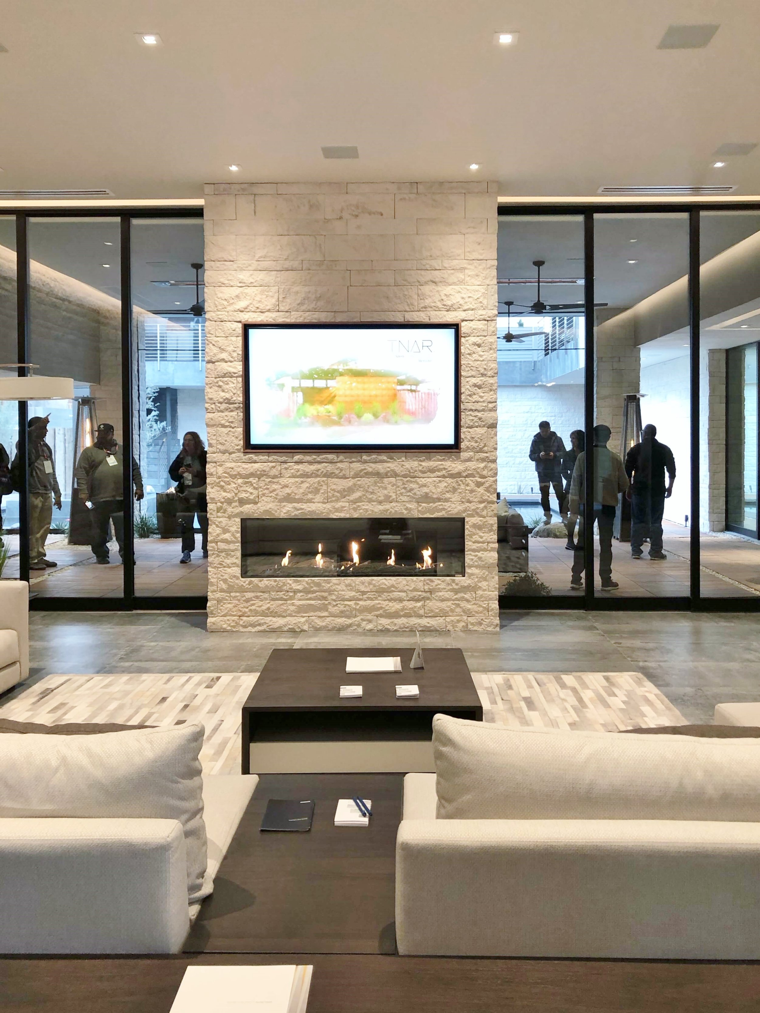 The spacious living room with floor to ceiling sliders and a modern stone fireplace handles lots of visitors at The New American Remodel 2019. #hometour #patio #contemporaryhome