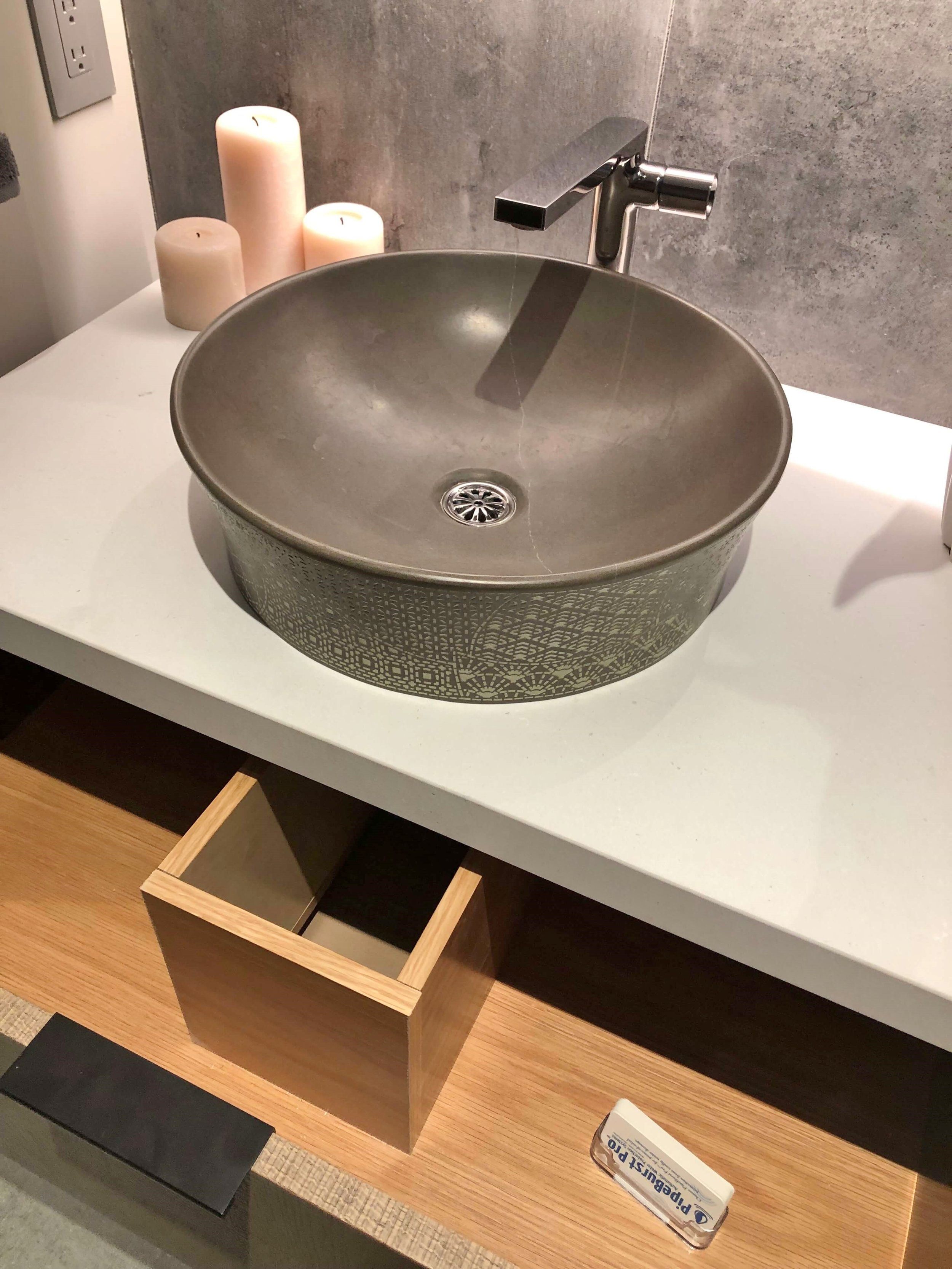 Textural pattern on the vessel sink with useful storage below in the powder room vanity. The New American Remodel 2019 #hometour #vesselsink #powderroom #contemporaryhome