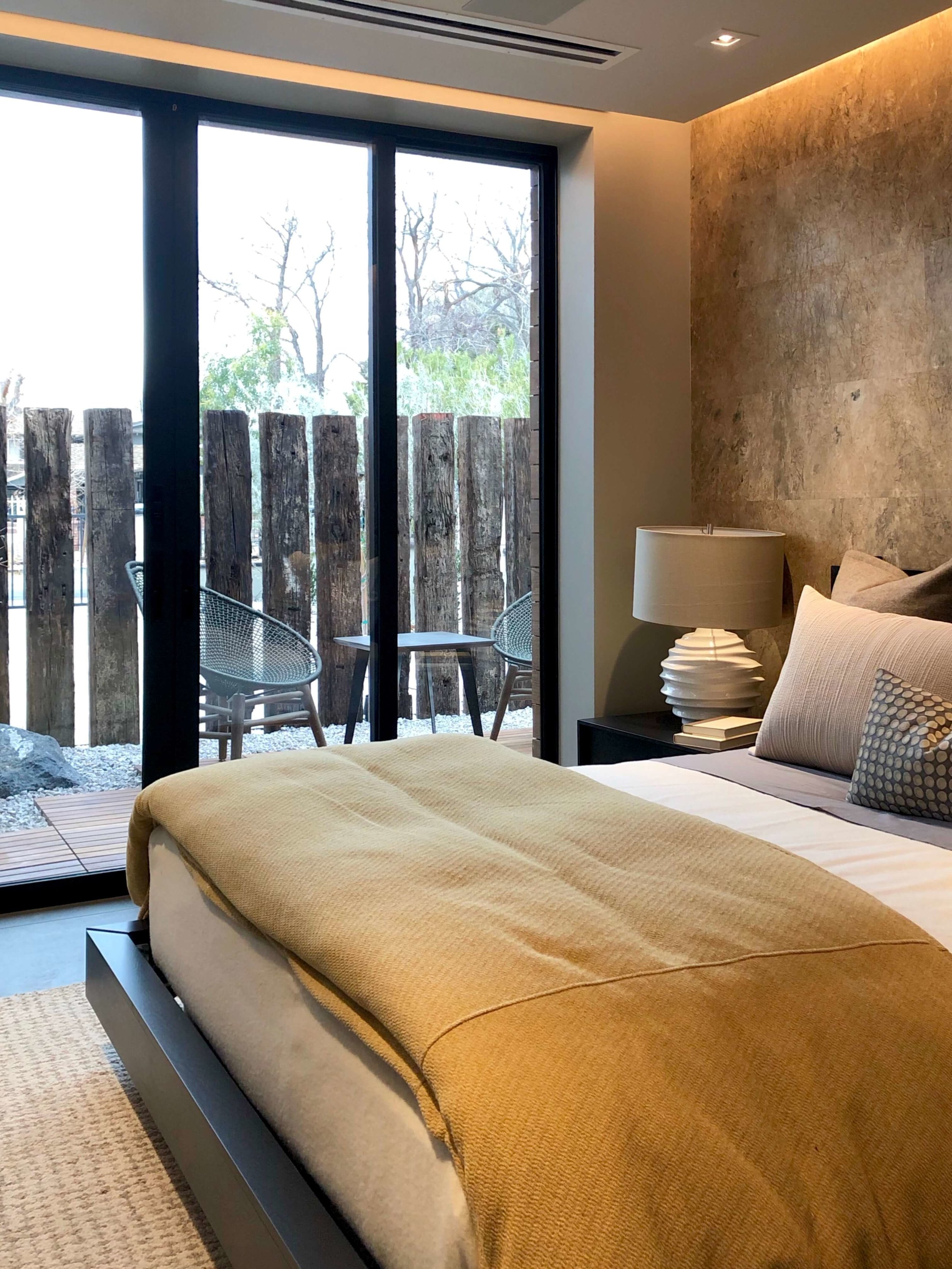Tone on tone textures create interest and warmth in the guest bedroom at The New American Remodel 2019. #hometour #patio #contemporaryhome #bedroom