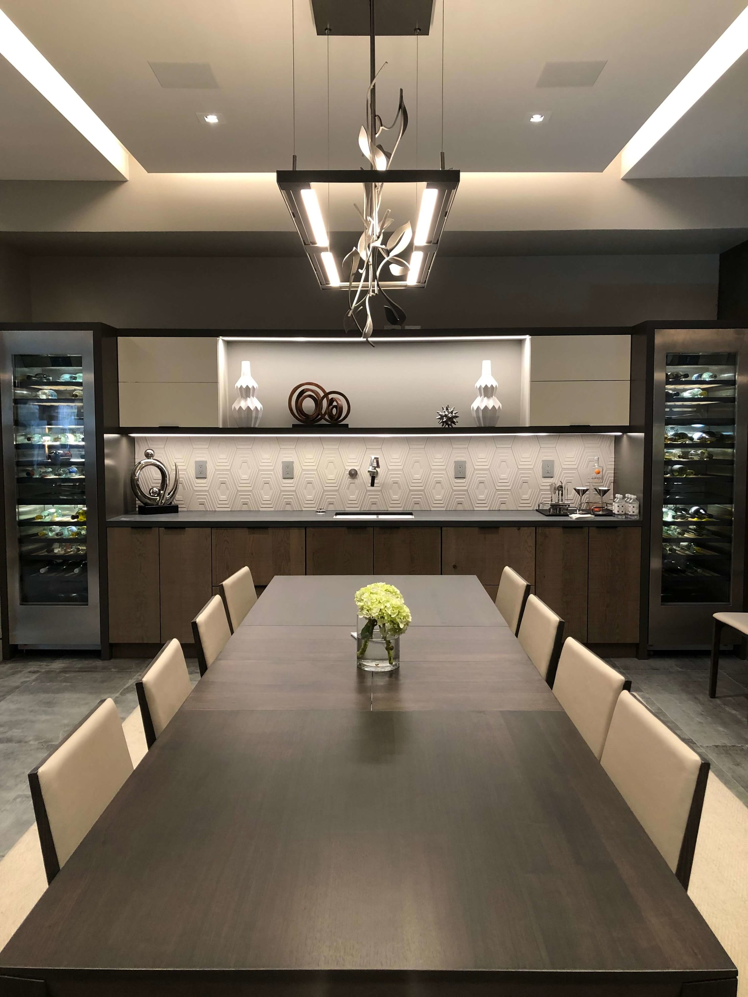 The spacious dining room had built in wine refrigeration, storage and a long dining table in The New American Remodel 2019. #hometour #contemporaryhome #diningroom