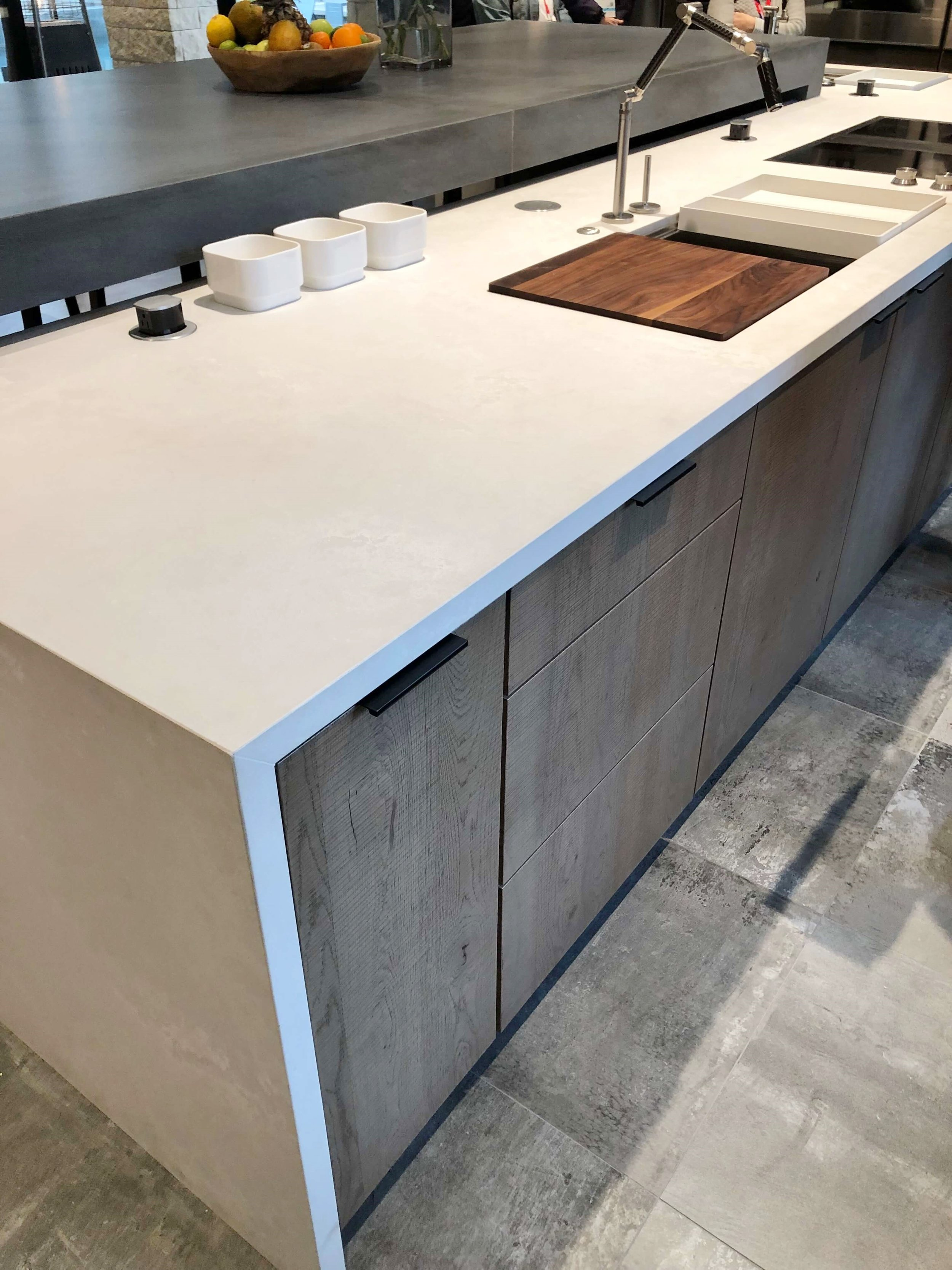 The waterfall edge kitchen island had flat front rustic wood paneled cabinetry below. Pop up outlets are located for convenience in the island. The New American Remodel 2019 #hometour #kitchenisland #kitchen #contemporaryhome