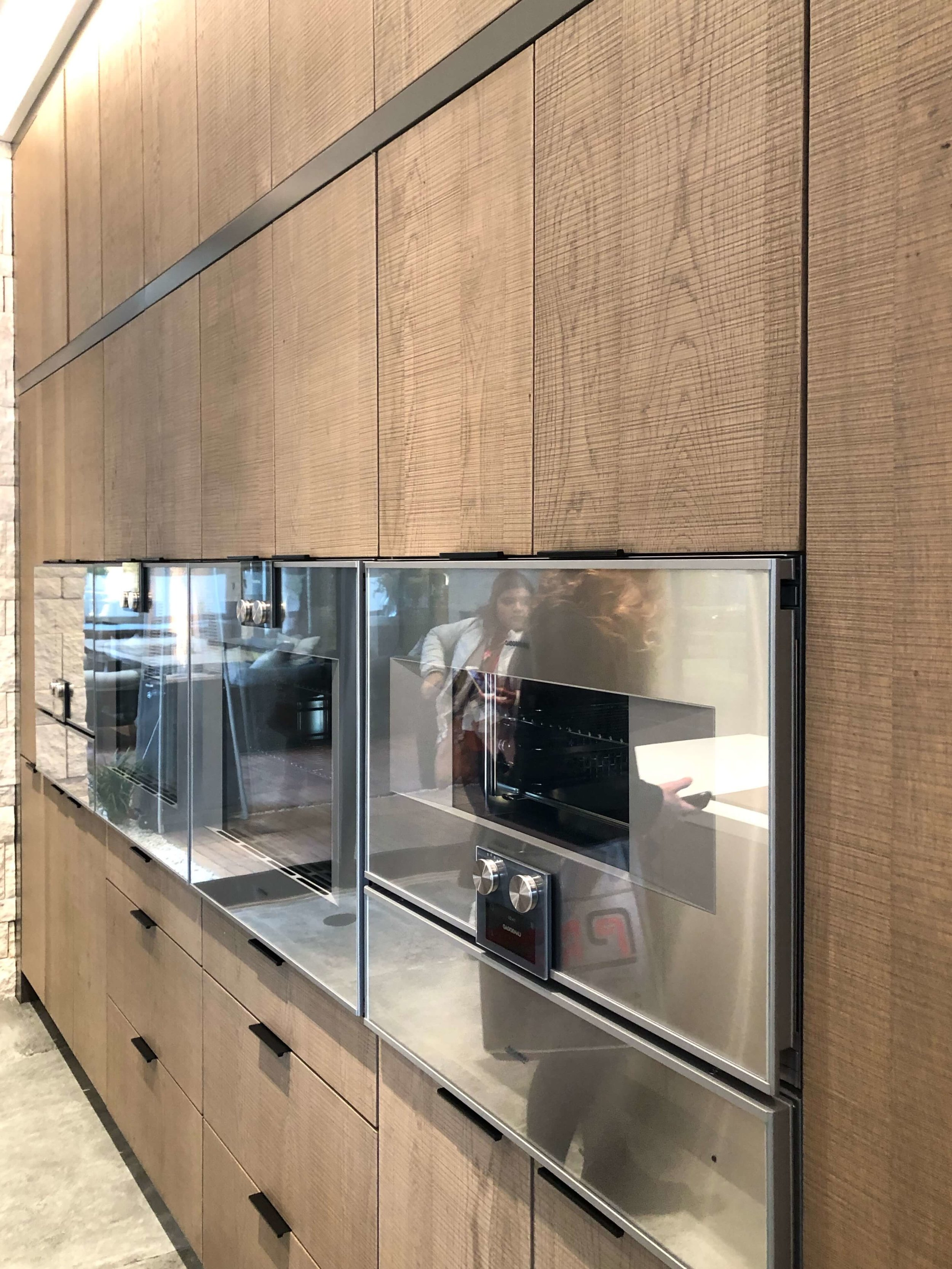 The wall of ovens and cabinetry meld together seamlessly in the kitchen of The New American Remodel 2019. #hometour #appliances #gaggenau #contemporaryhome