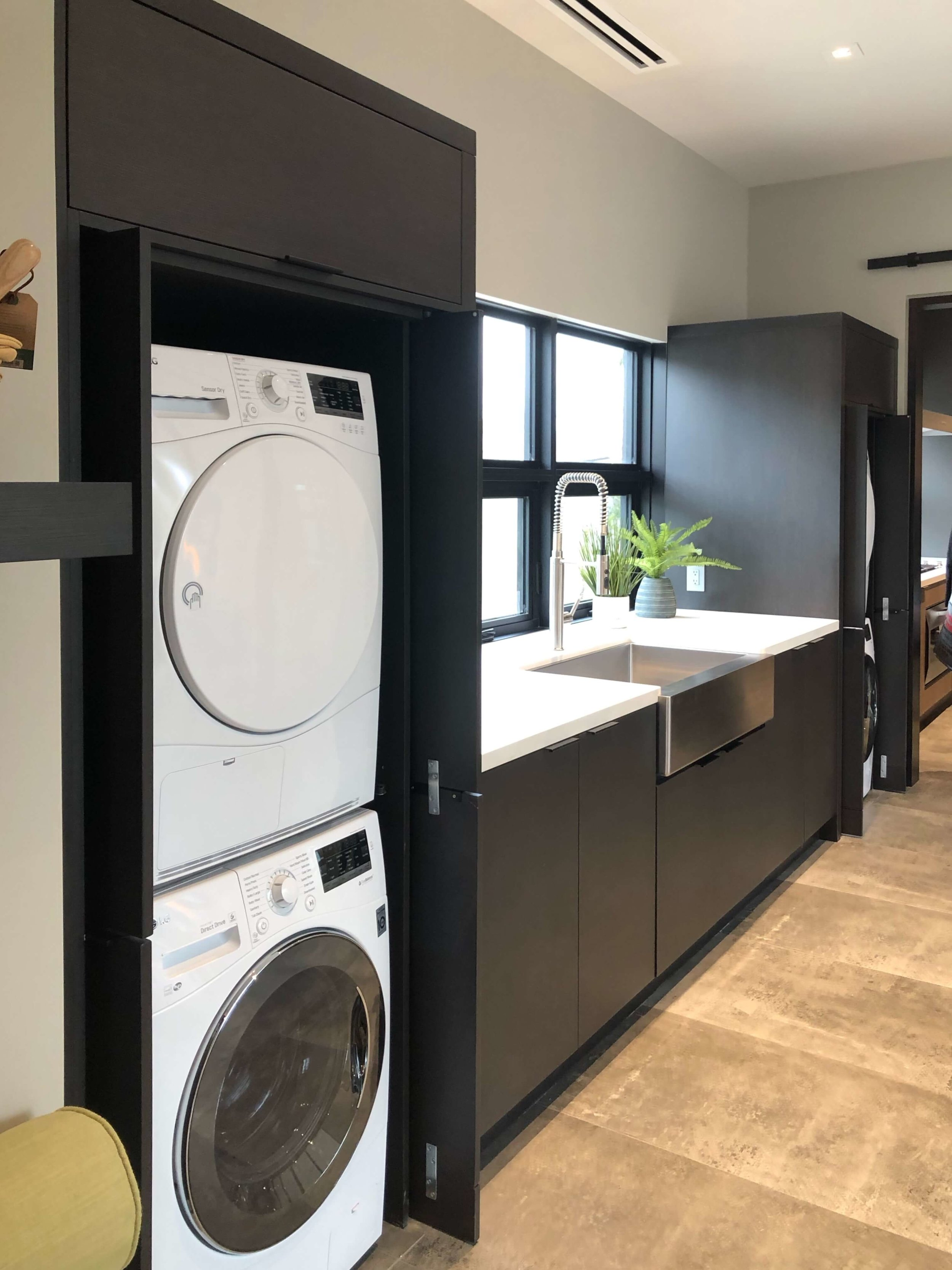 Laundry room with two sets of stacked washer / dryers and a large stainless farmhouse sink in The New American Remodel 2019. #laundryroom #farmhousesink #hometour #contemporaryhome