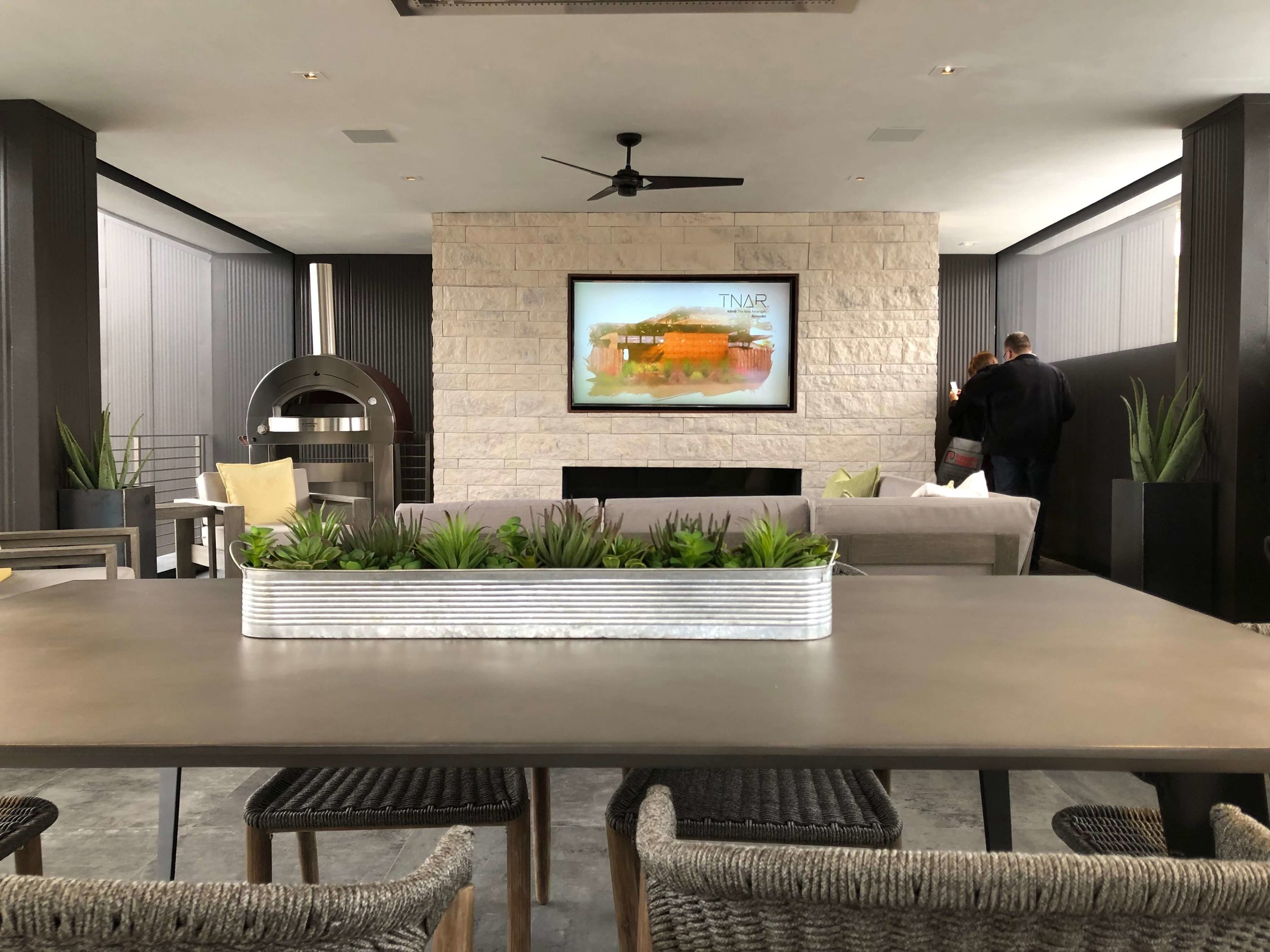 This outdoor living lounge area has a kitchen, fireplace with tv, seating and dining spaces, even a pizza oven! The New American Remodel 2019. #gameroom #outdoorliving #hometour #contemporaryhome