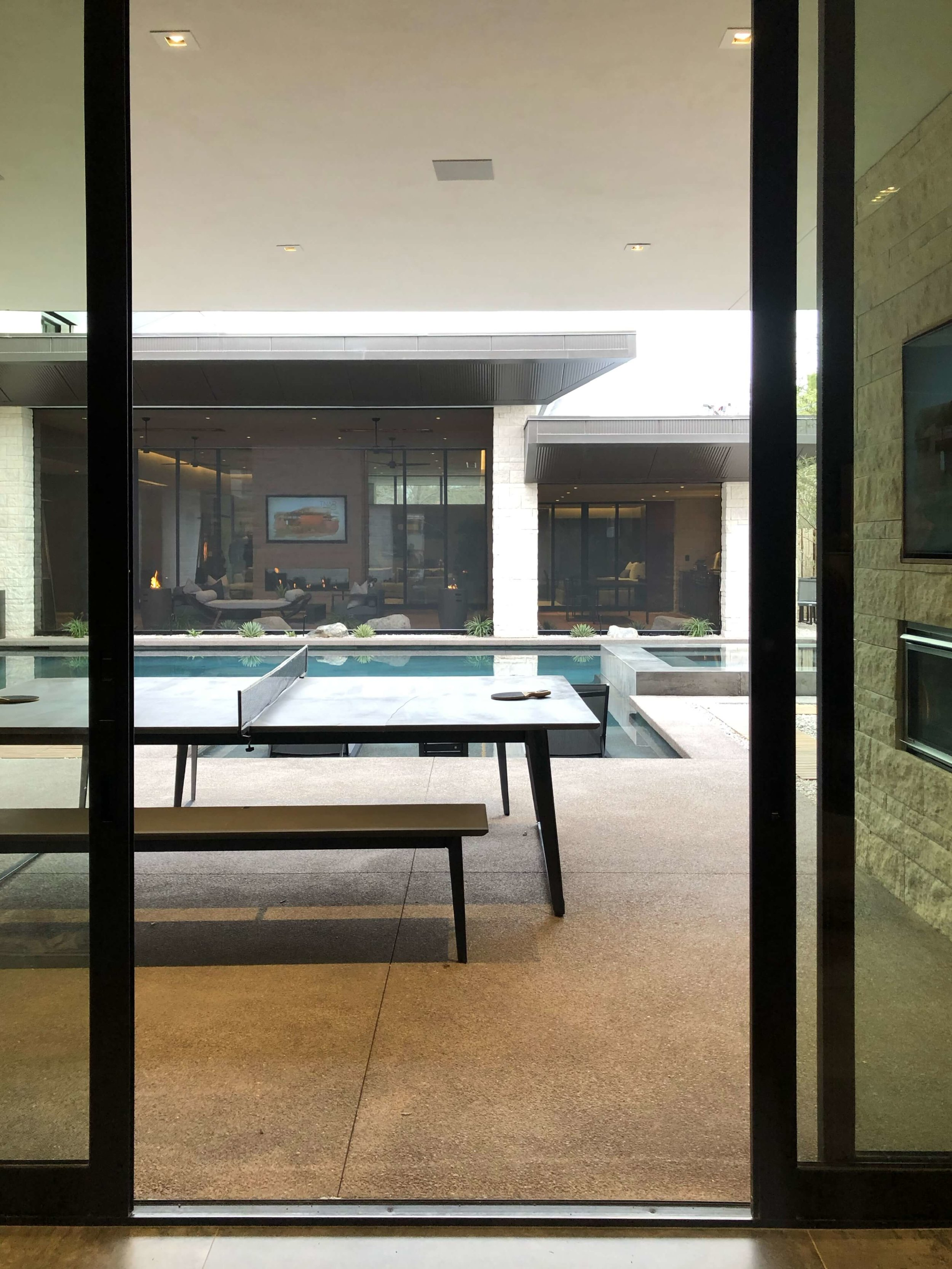 Ping pong table area by the pool with outdoor fireplace and tv in The New American Remodel 2019. #gameroom #outdoorliving #hometour #contemporaryhome