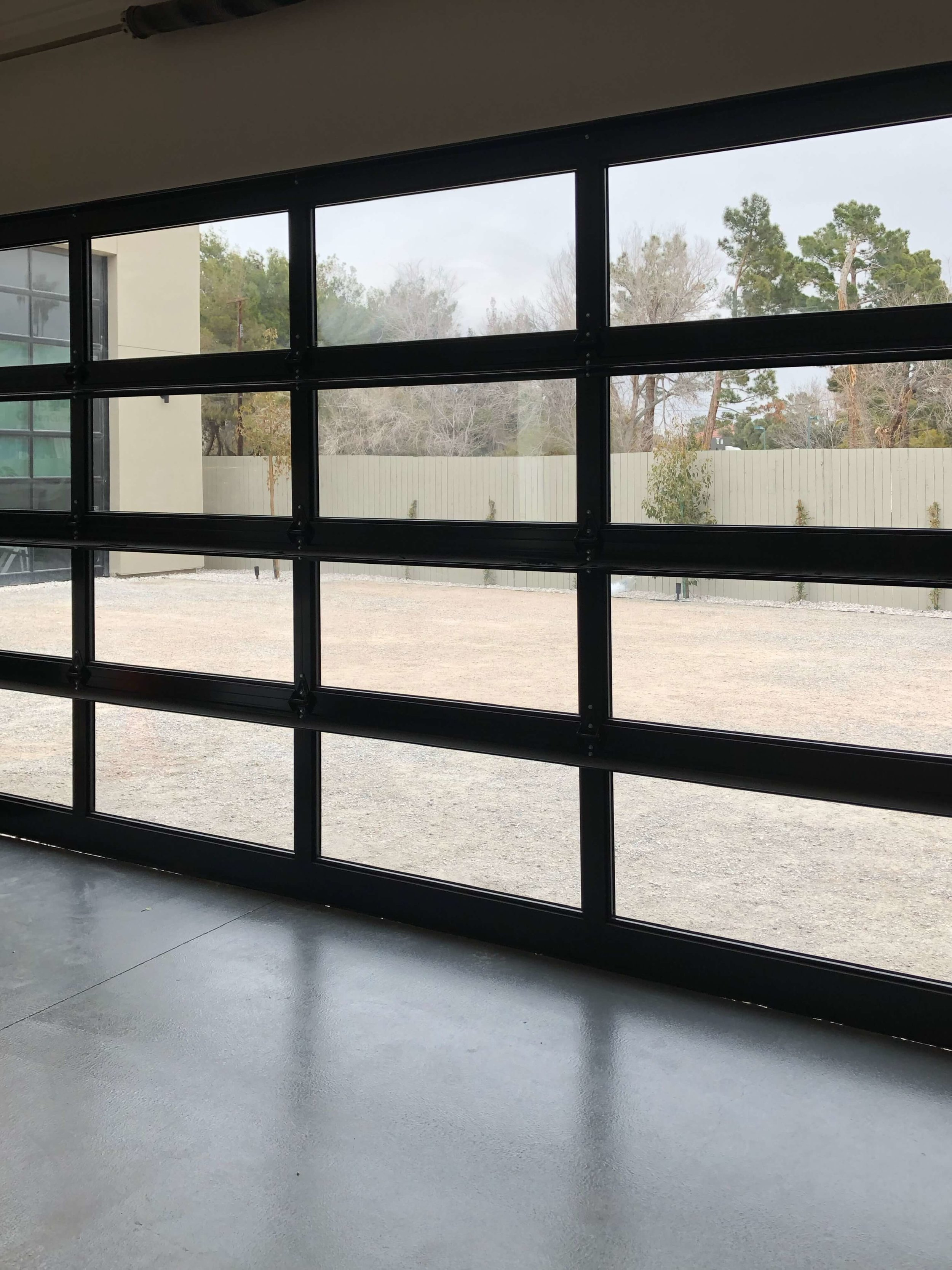 Glass garage door, mirrored on outside at The New American Remodel 2019. #garage #hometour #contemporaryhome