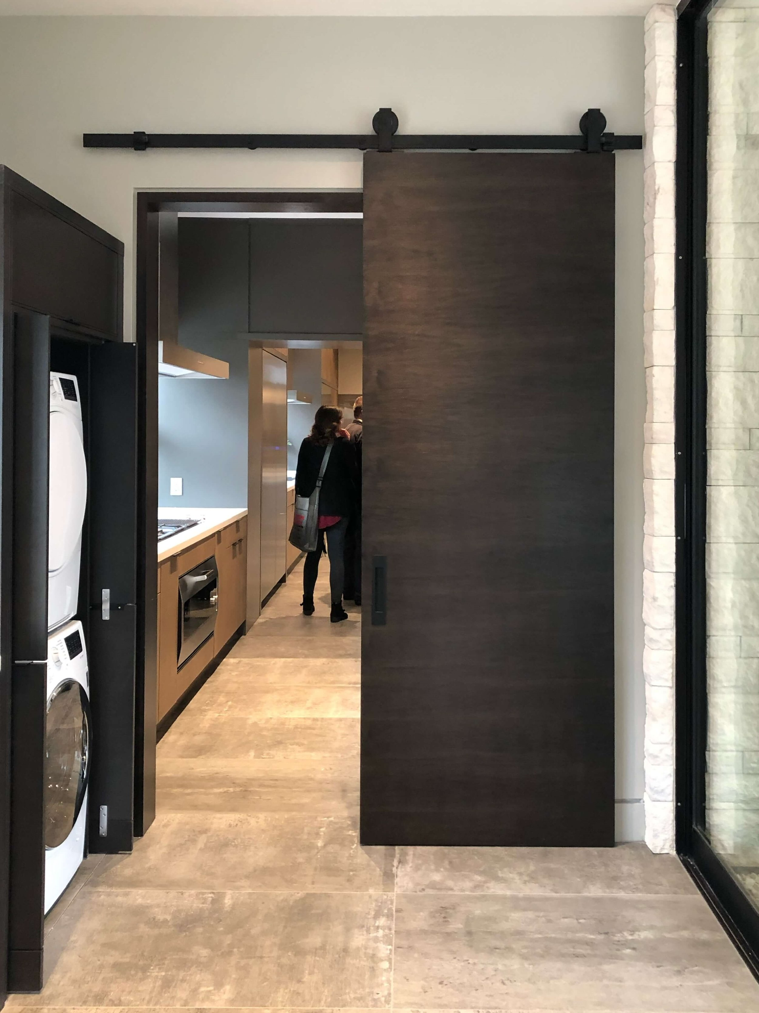 Contemporary tall wood barn door closes off the laundry room when needed in The New American Remodel 2019. #hometour #contemporaryhome #laundryroom #barndoor