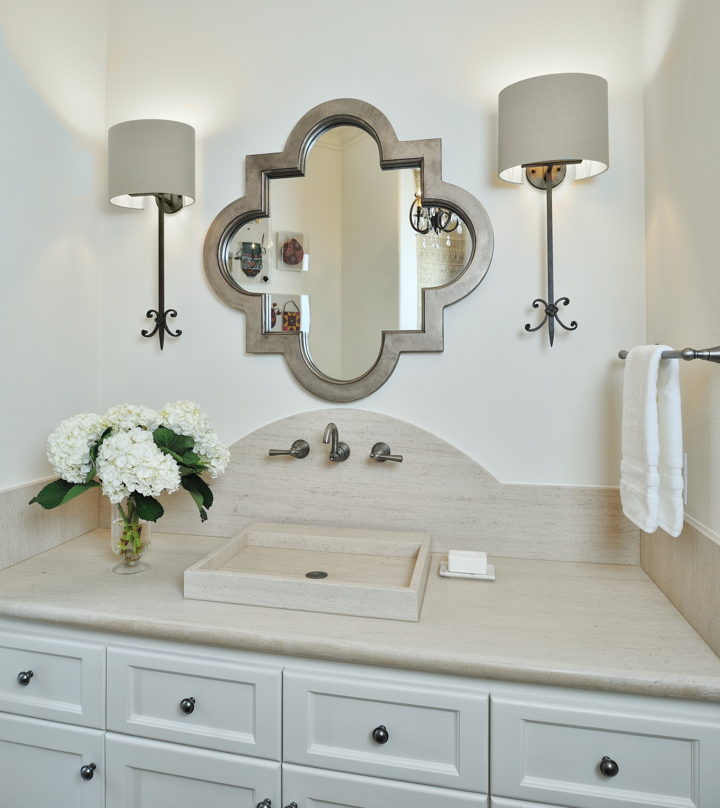 HOME TOUR - The limestone counter, curved splash and sink create a simple, seamless look in this powder bath. The quatrefoil custom mirror and sconces add interest. Carla Aston, Designer | Miro Dvorscak, Photographer #bohostyle #hometour #remodel #powderbath
