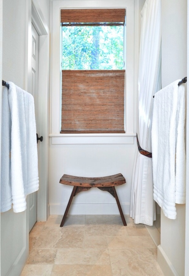Hallway to the shower in the master bath has a spa-like feel with a rustic stool. Carla Aston, Designer | Miro Dvorscak, Photographer #bathroomremodel #spalike