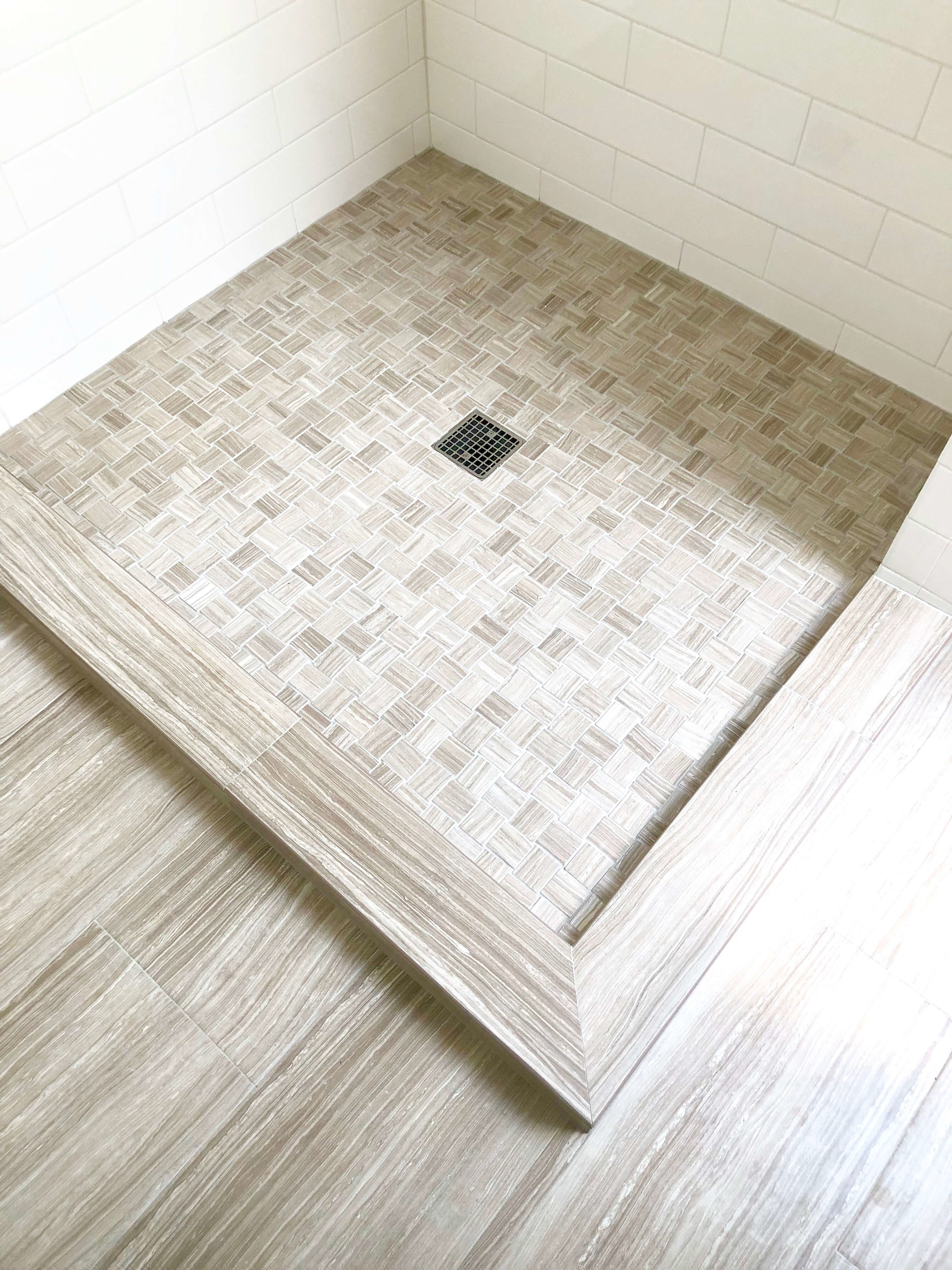 Shower curb done in tile to match the floor expands the look of this small bathroom. A frameless glass enclosure on top will help reinforce this open feeling. #showerstall #bathroomdesign
