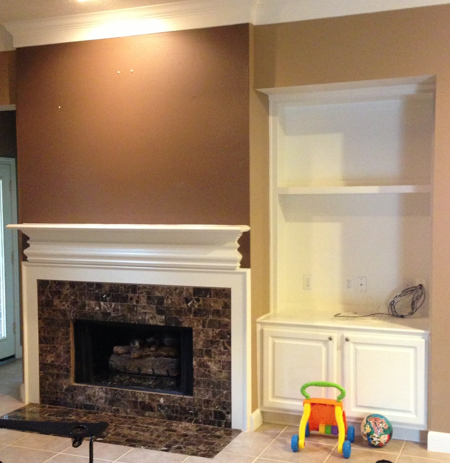 This fireplace mantel was originally designed to fit the wall, without regard to scale or how it related to the surround below.