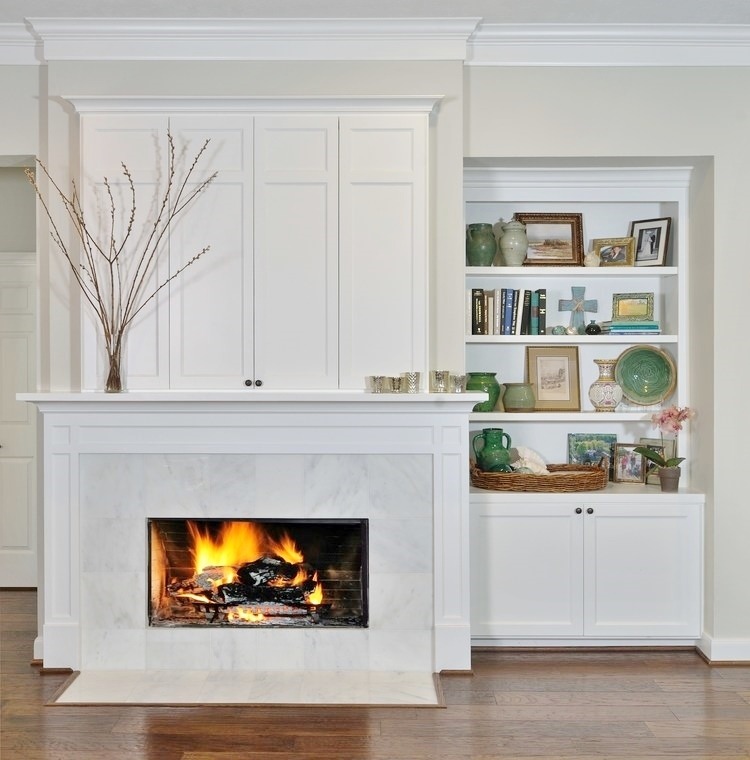 This fireplace mantel and surround with tv cabinet above are appropriately scaled for this wall and all other elements in the space. Carla Aston, Designer   Miro Dvorscak, Photographer #mouldings #fireplacemantel #mantle