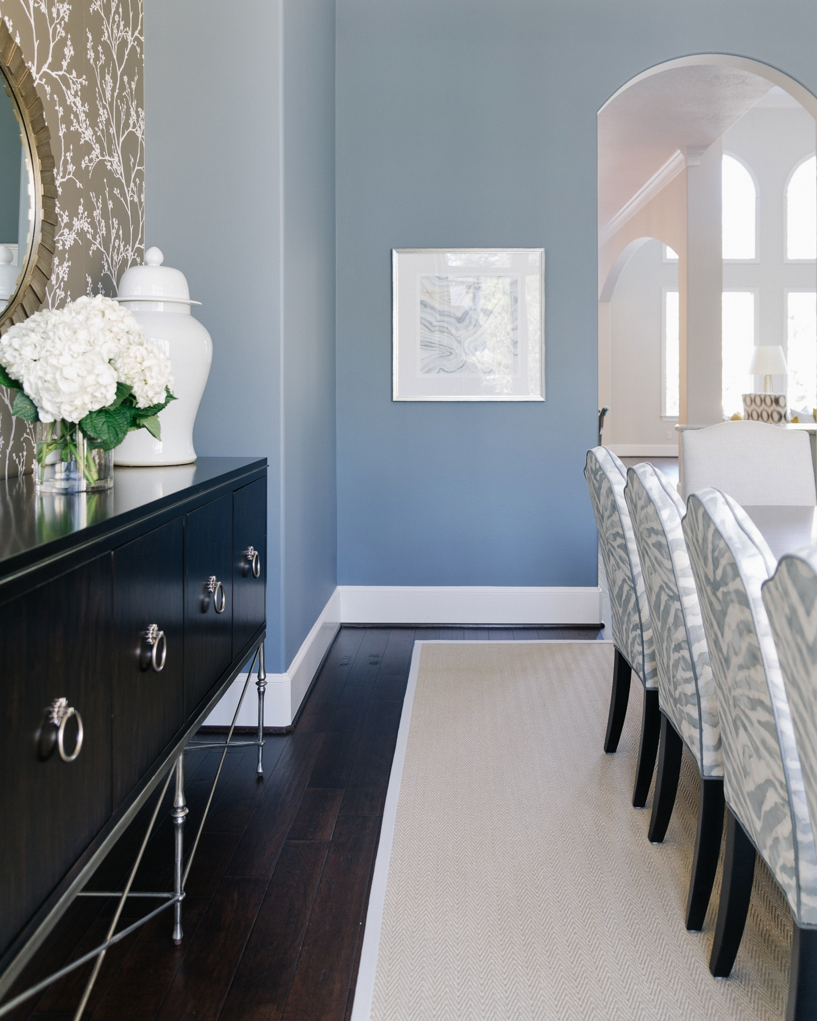 Light sisal, natural fiber rug in this dining room gave a more informal and fresh look to the space. Blue dining room, Designer: Carla Aston, Photographer: Colleen Scott | #diningroom #sisalrug #diningroomideas #naturalfiberrug