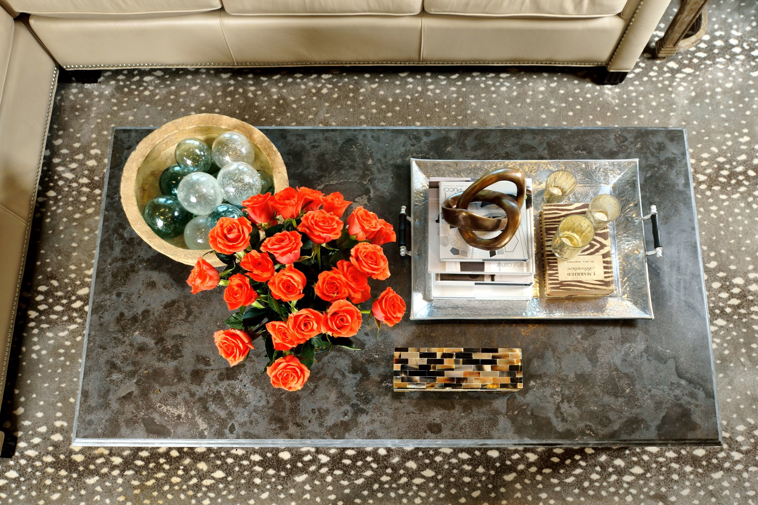 The antelope pattern rug here sets off this natural stone coffee table and it's decor, perfectly. #animalprintcarpet #rugideas #coffeetabledecor