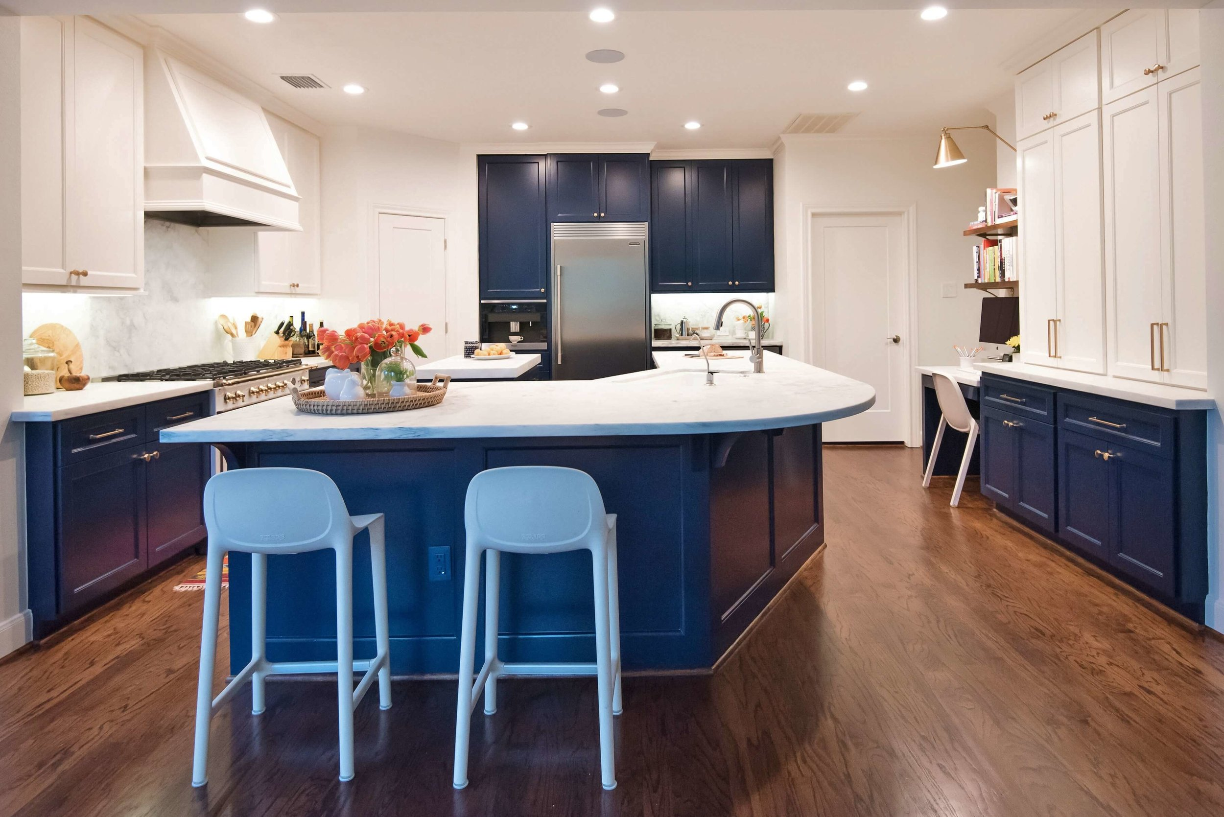 AFTER - We removed the column with this remodel, adding a beam across the wide kitchen opening and then lowered to bar to counter height. The bar face was paneled and painted to match the blue kitchen cabinets. These changes really help the bar feel more like part of the kitchen and appear larger and more open. | Carla Aston, Designer | Lauren Giles, Photographer #bluekitchen #kitchendesign #kitchenbar