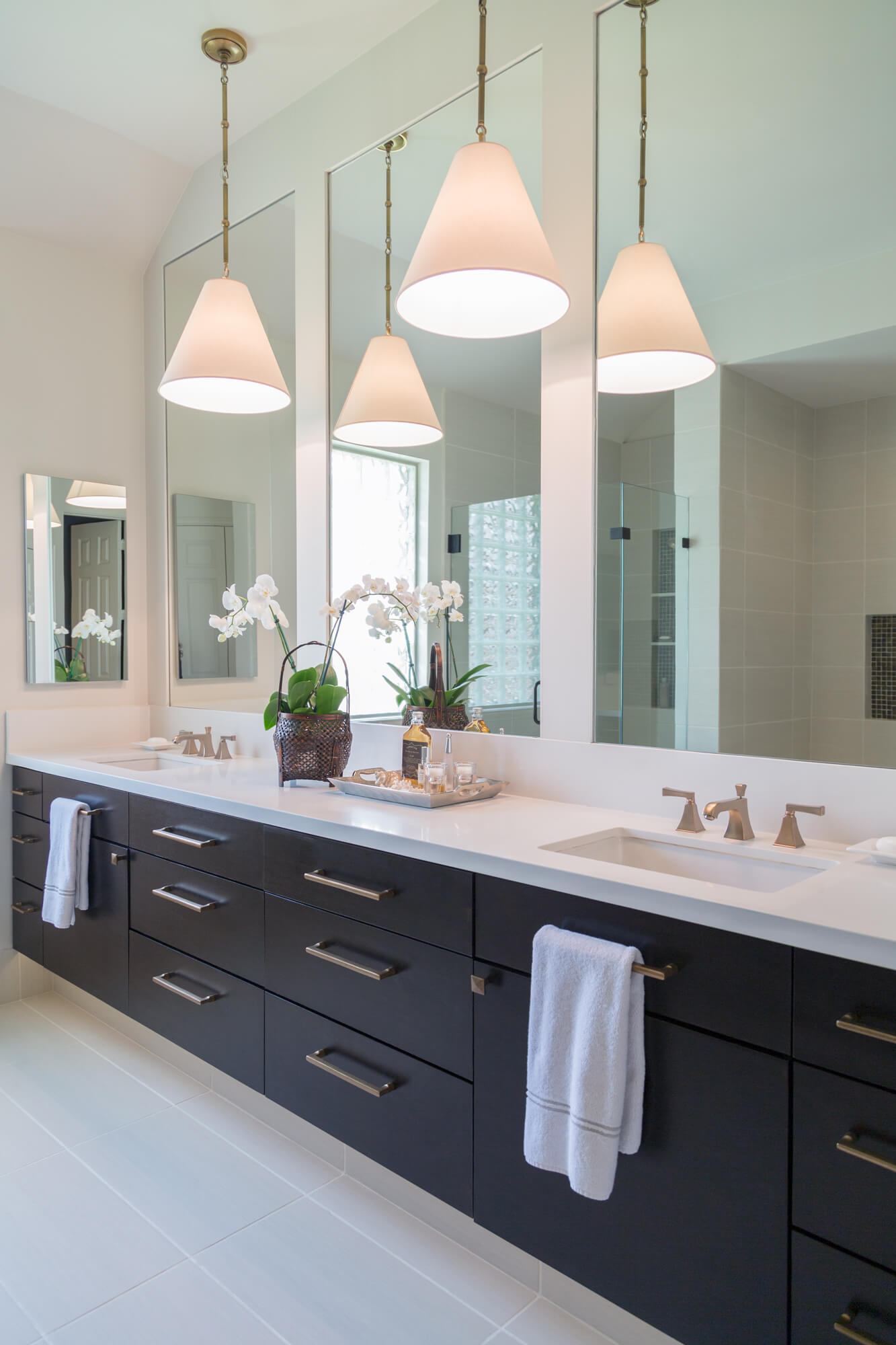Floating linear look bathroom vanity in an espresso stain gives an open and more modern look in this remodel. Carla Aston, Designer | Tori Aston, Photographer #floatingvanity #bathroomdesignideas #modernbathroom
