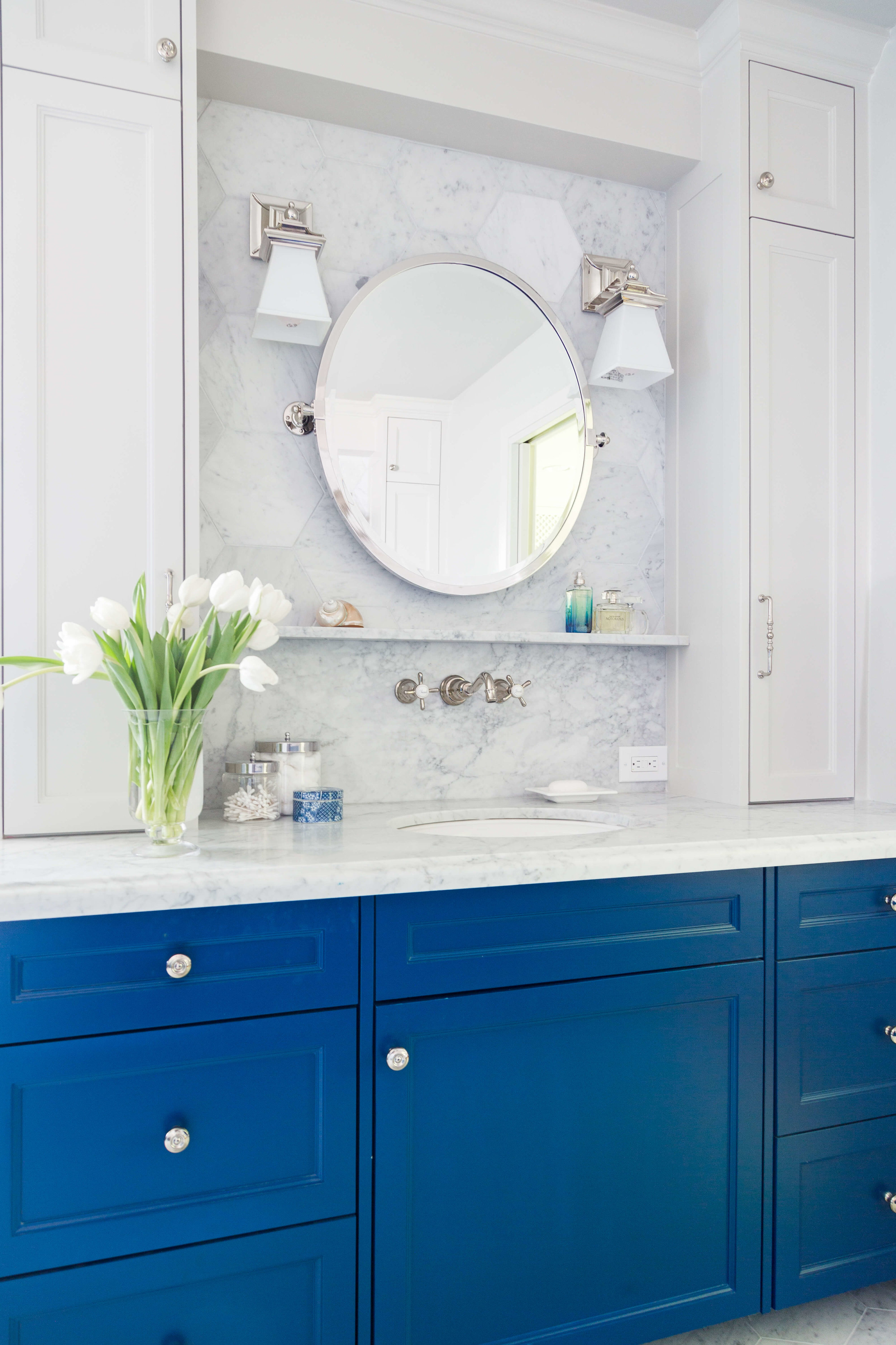 The two toned look of this bathroom cabinetry gives a lighter look to the upper vanity area of this master bath, as well as creating some additional storage. Carla Aston, Designer | Tori Aston, Photographer #bathroomvanity #bathroomdesign #bathroomcabinetry
