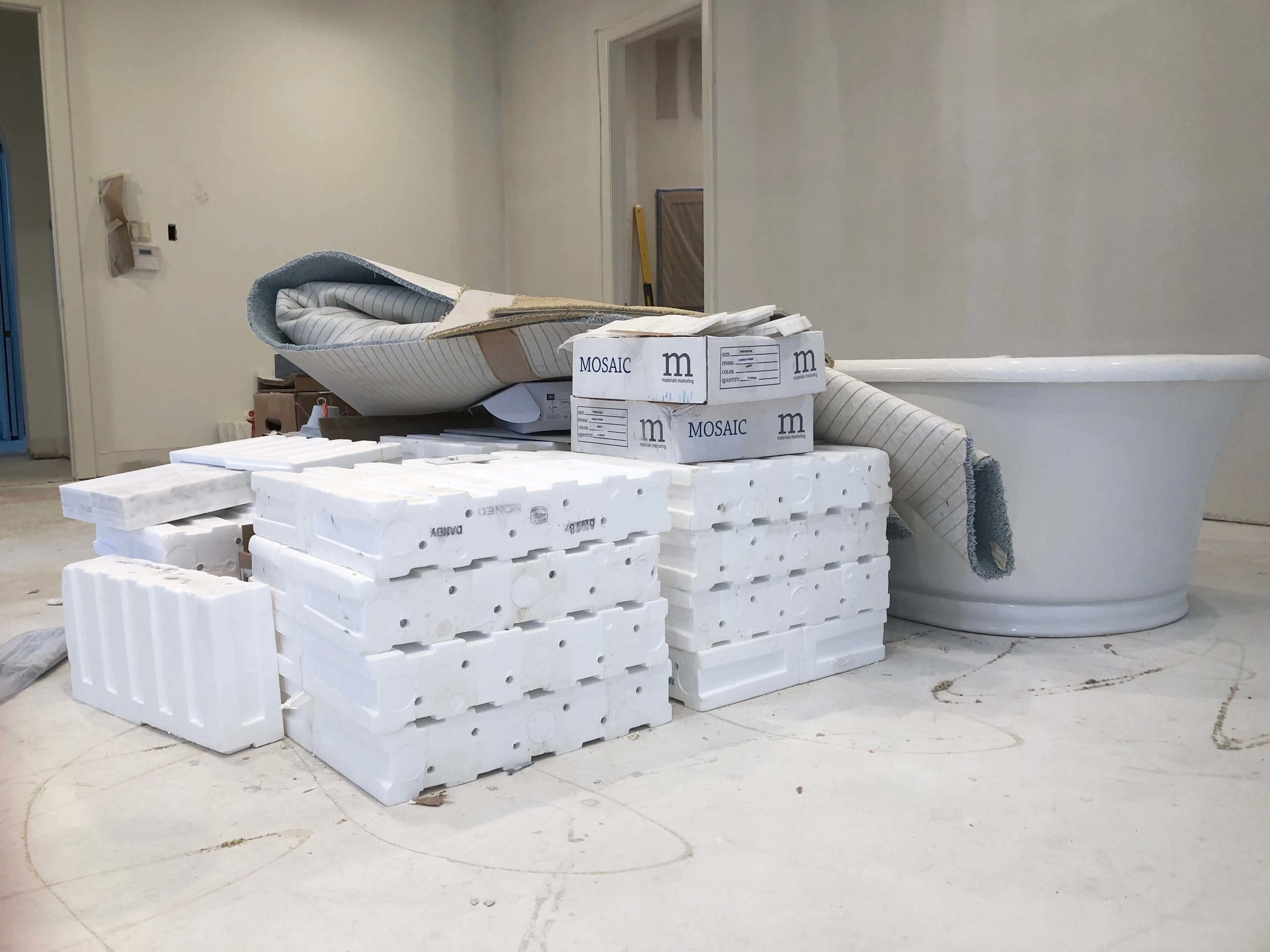 Stacks of tile and new tub on a remodel job site. How did these get here? If you're a designer and you are buying these products for your clients, you need to think this through.