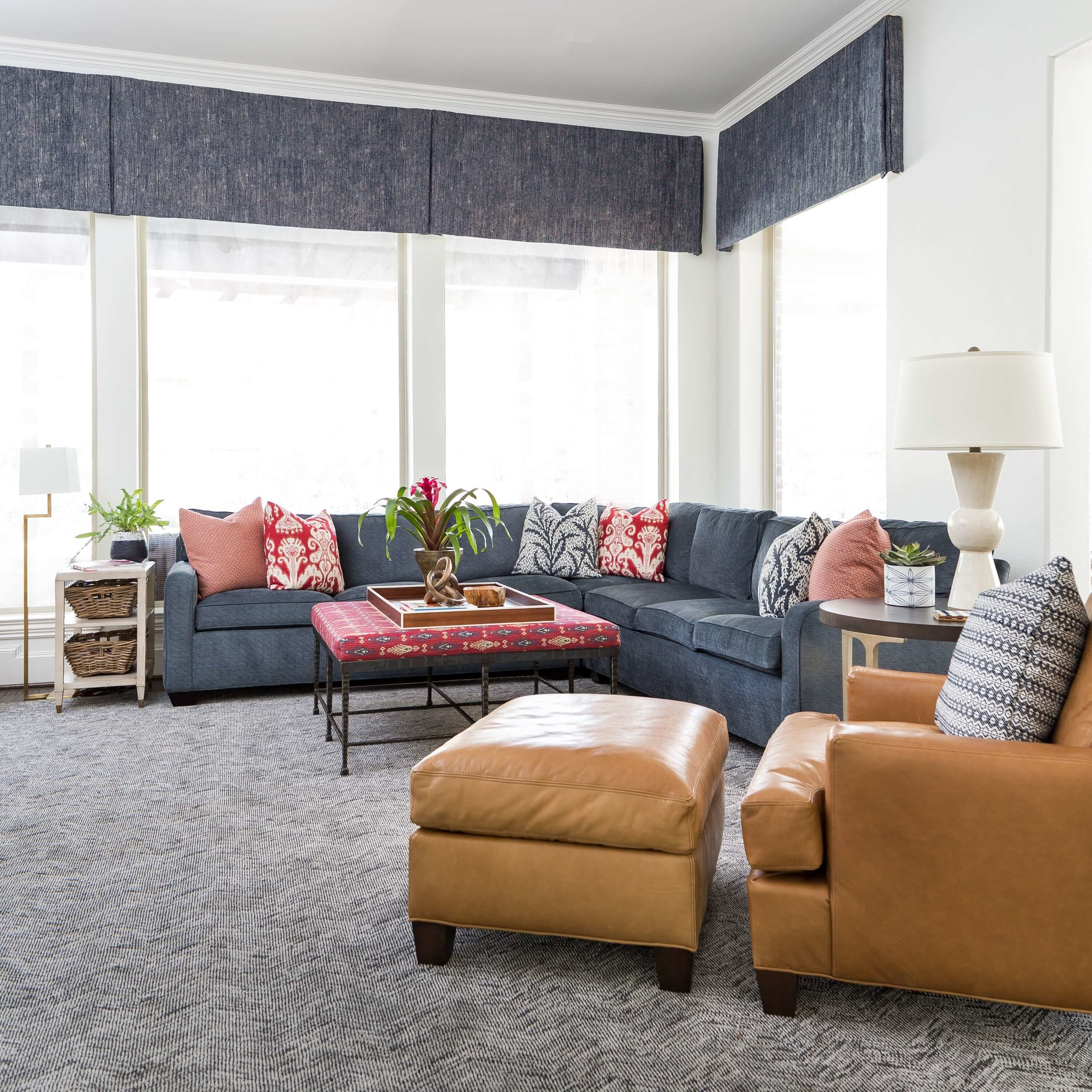 Family room with red patterned decorative pillows on a navy sofa add color and life to the room. | Interior Designer: Carla Aston #pillows #patternedpillows #redpillows #homedecor