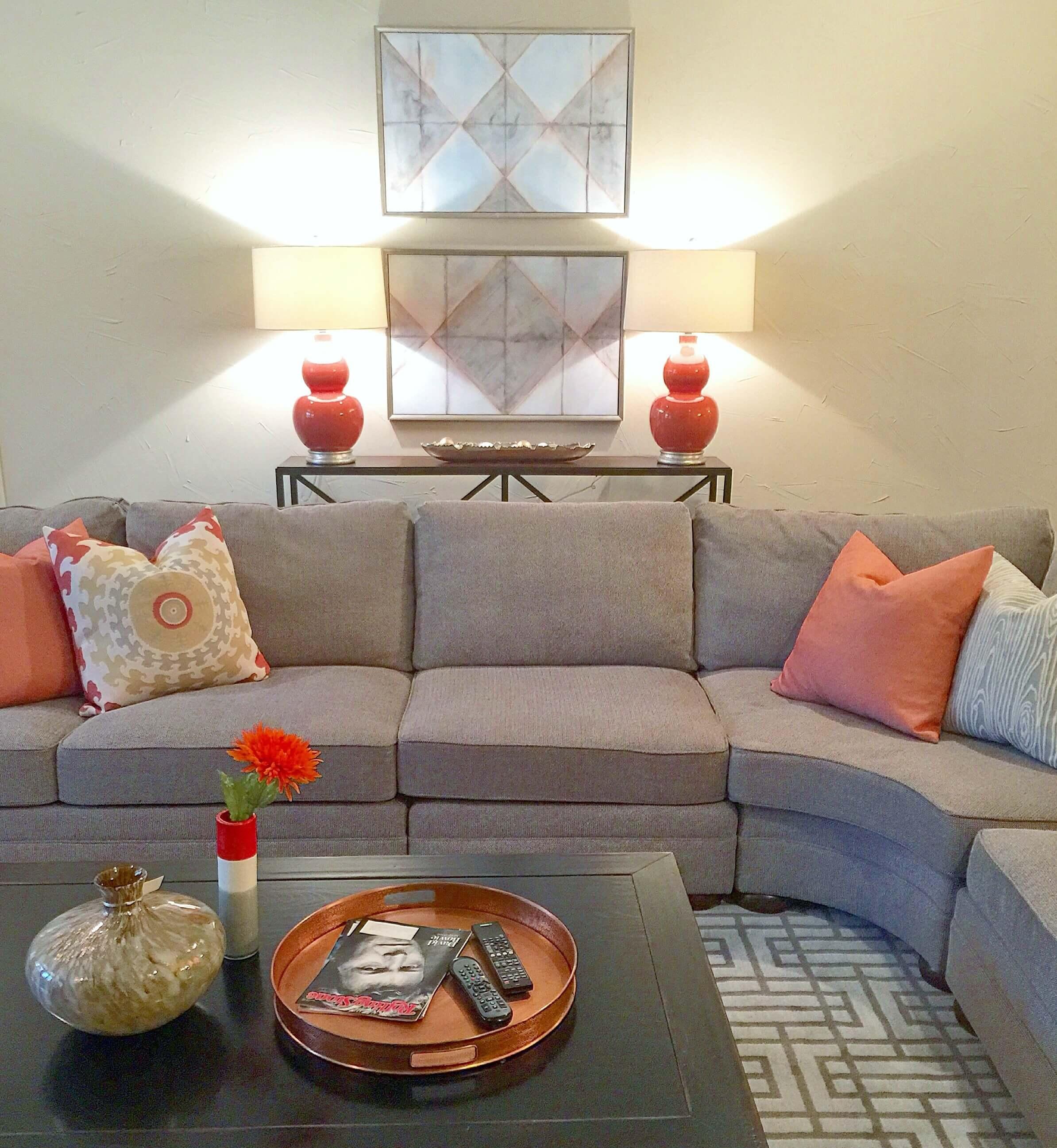 Orange pillows and accessories add some life to this gray sofa. Carla Aston, Designer #pillows #livingroom #homedecor #livingroomideas