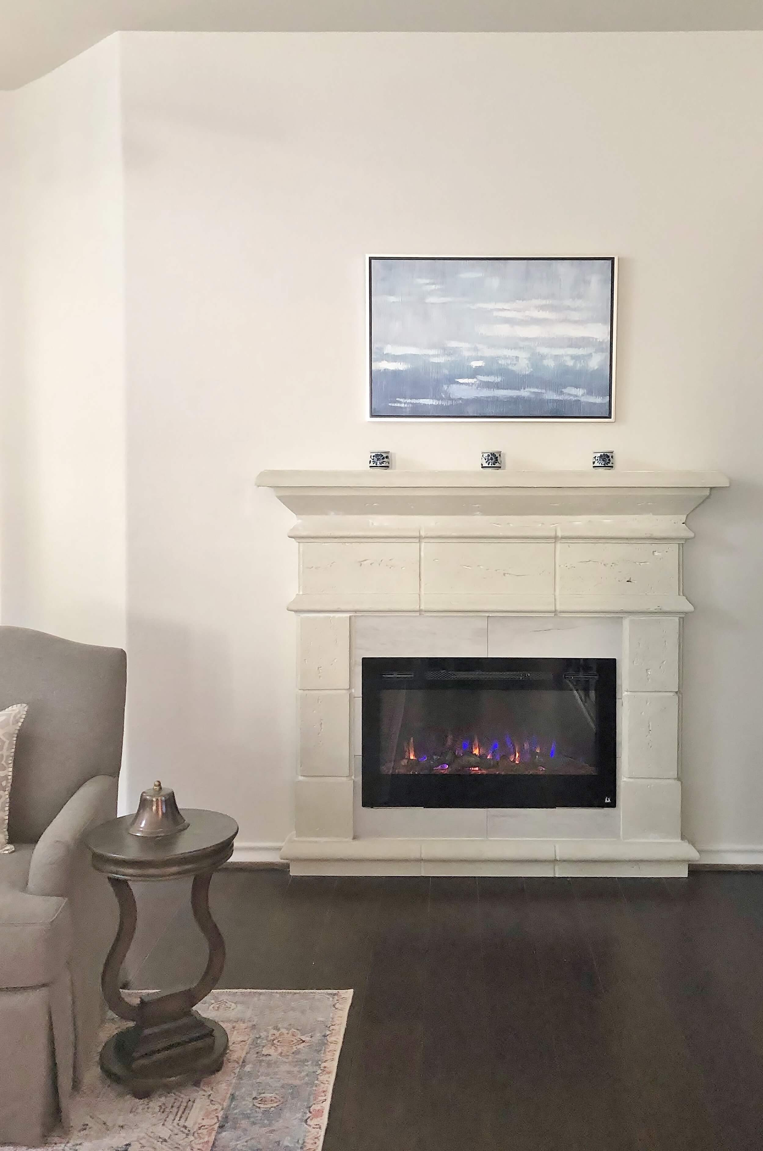 An electric fireplace looks so real with this cast stone mantel.