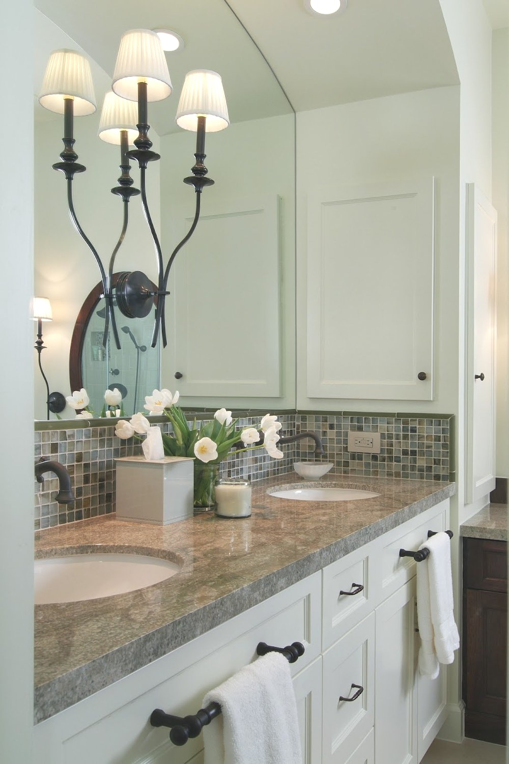 A central double wall sconce works well with in this bathroom between two sinks. Carla Aston, Designer #bathlight #vanitylight #wallsconce