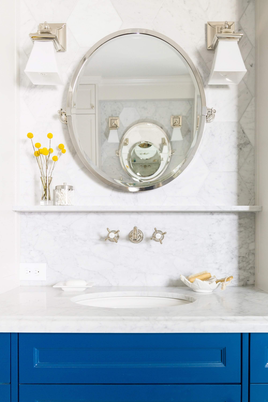 Love the sconces used with this pivot mirror on top of the hex white marble tiles. Carla Aston, Designer | Tori Aston, Photographer #wallsconces #vanitylight #bathroomlighting #bathroomdesign
