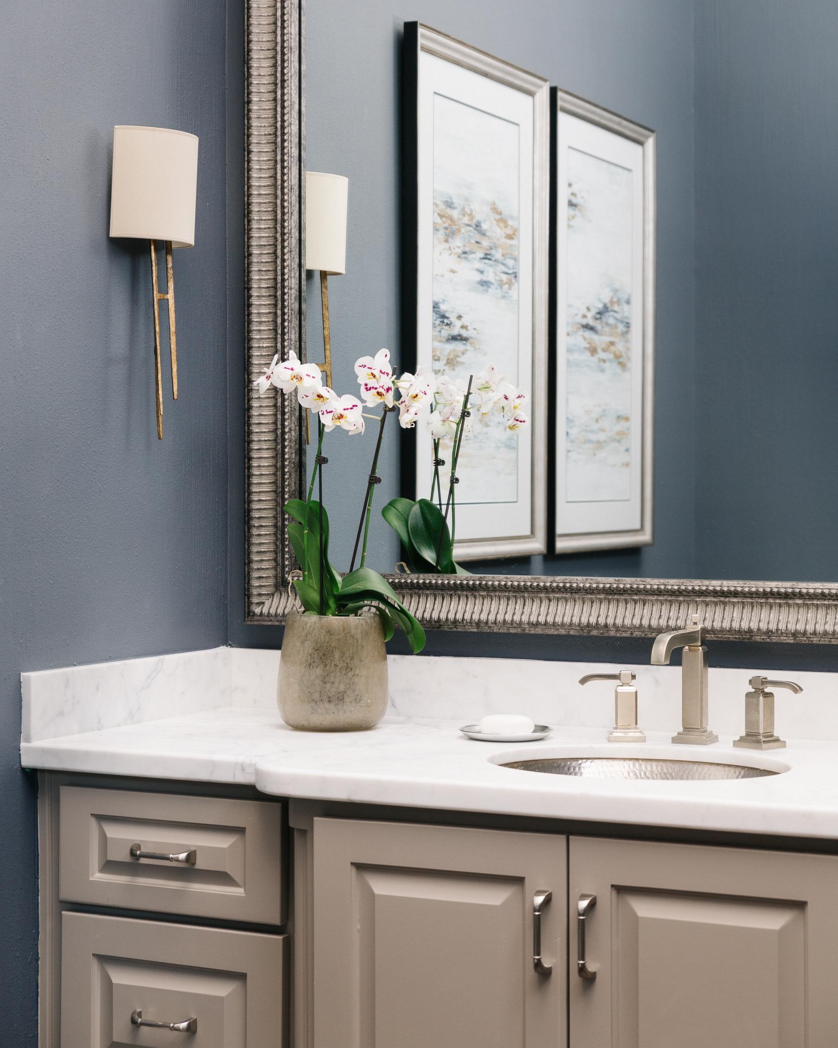 A beautiful powder room with wall sconces on the side walls of the vanity. Carla Aston, Designer | Colleen Scott, Photographer #wallsconces #vanitylight #bathroomlighting #bathroomdesign