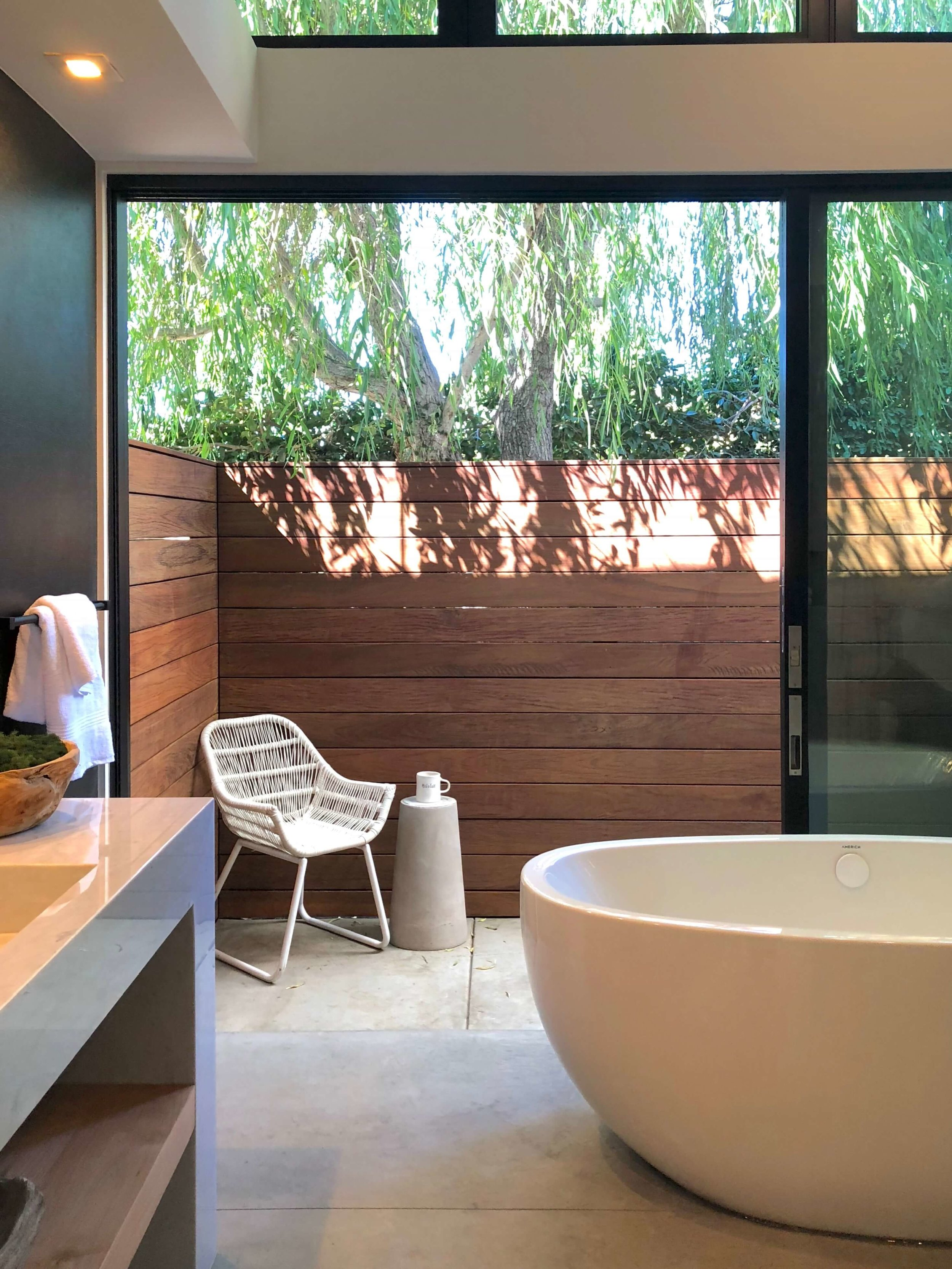 The free standing tub allows access to the patio beyond around it's curves, in this modern bathroom design by Vitus Matare. #tub #freestandingtub #bathroomdesign #bathroomideas