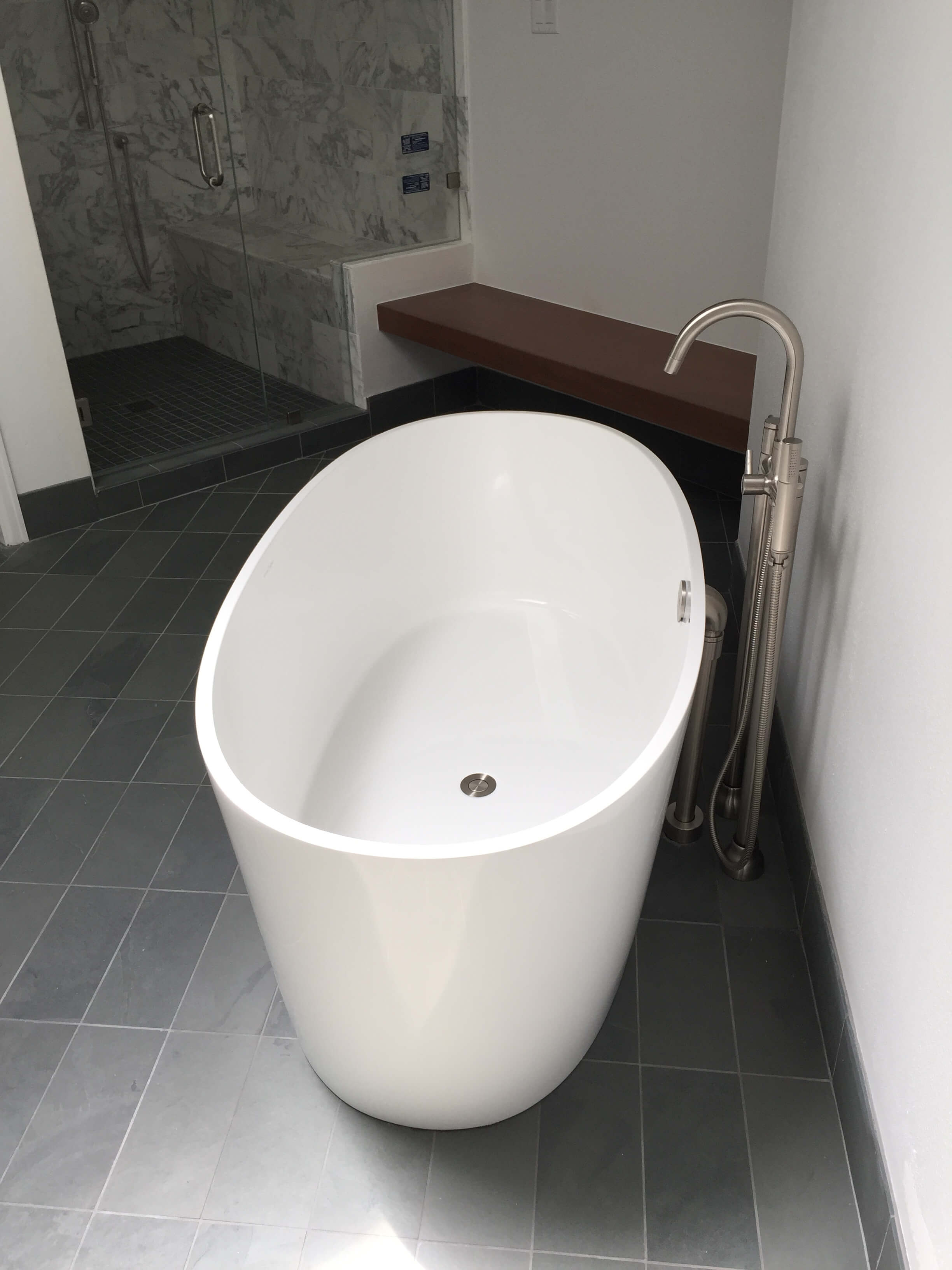 AFTER  - This sleek, free standing tub took up much less floor space than its deck mounted predecessor. The floor tile surrounding it's sculptural shape gives the bathroom a much lighter and up to date look. Carla Aston, Designer | #bathroomremodel #tub #bathroomdesign #freestandingtub