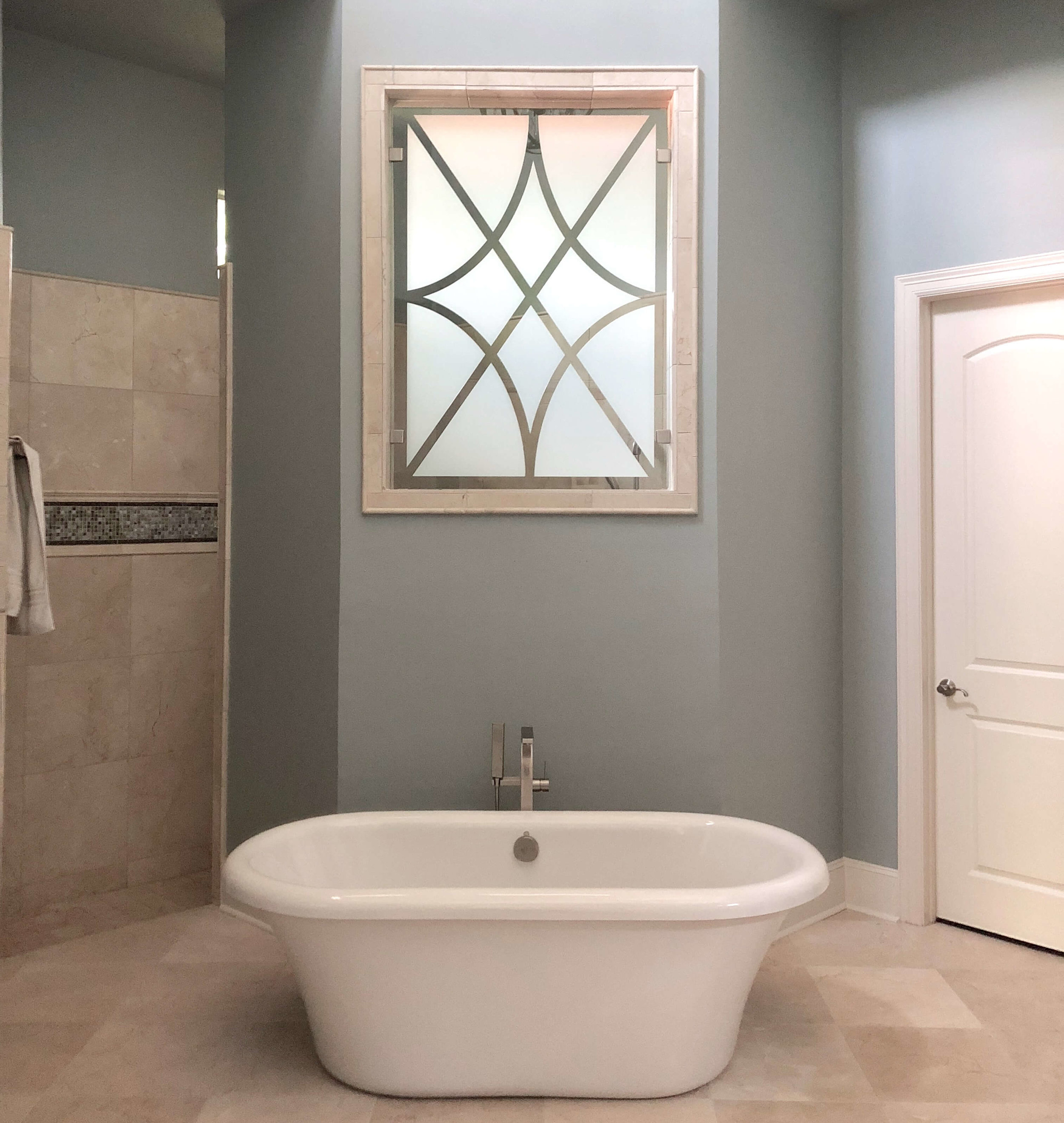 AFTER  - A free standing tub added a light touch in this bathroom. Note the window film pattern we added on to the glass above. Carla Aston, Designer | #freestandingtub #tub #bathroomdesign #windowfilm #bathroomideas